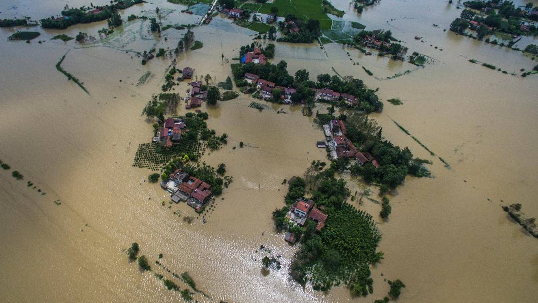 This Wednesday, July, 20, 2016 photo released by Xinhua News Agency, shows village houses and field partially submerged by flood waters in Gaoyang Town, Shayang County, central China's Hubei Province. China says dozens of people have died or gone missing since Monday in massive floods across the country's north. (Xiao Yijiu/Xinhua via AP)