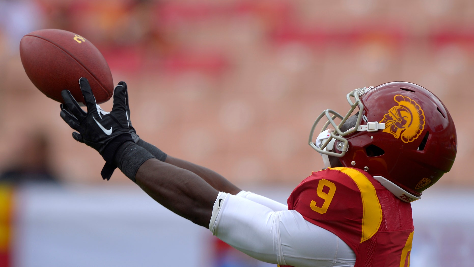 FILE - In this Sept. 21, 2013, file photo, Southern California wide receiver Marqise Lee catches a pass during warm-ups prior to an NCAA college football game against Utah State in Los Angeles. Already depleted by NCAA sanctions, USC is rapidly running out of healthy players midway through its tumultuous season. (AP Photo/Mark J. Terrill, File)