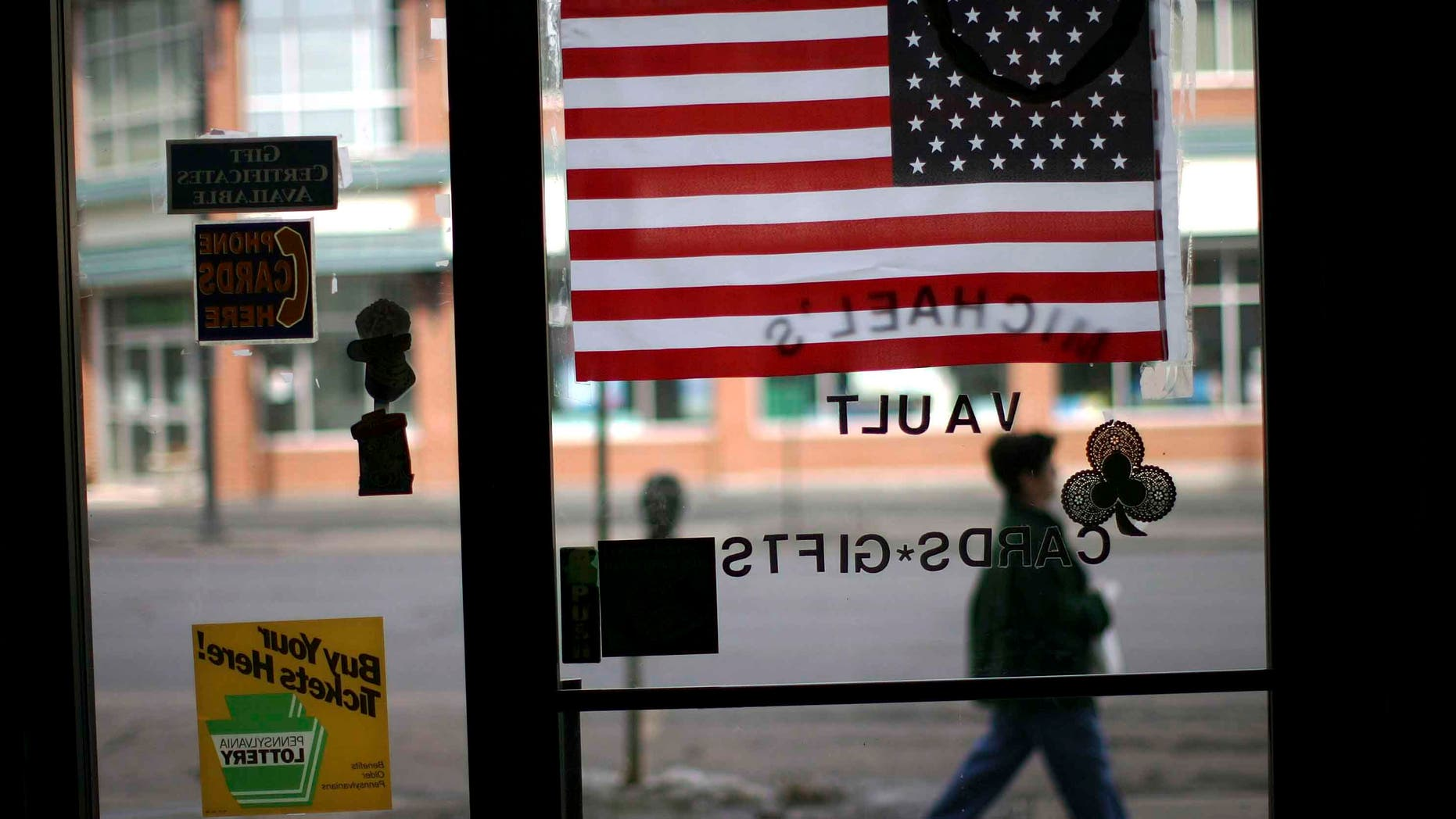 HAZLETON, PA - MARCH 14:  A woman walks pass an American flag in a store window March 14, 2007 in Hazleton, Pennsylvania. A new city ordinance in Hazleton has caused members of the large Latino community to fear discrimination and have concern for their future in the town. The city of Hazleton and its aggressive policy on illegal immigration is the subject of a federal trial that is being viewed nationally as a landmark case on immigration. In a move that caused outrage among Latino residents this past summer, city officials in Hazleton adopted ordinances that target illegal immigrants in housing, language use and employment. The ordinance, called the Illegal immigration Relief Act, has been put on hold while the case is challenged in federal court in Scranton by the American Civil Liberties Union and the Puerto Rican Legal Defense and Education Fund. At least 80 towns and cities across the nation have adopted similar measures against illegal immigrants.  (Photo by Spencer Platt/Getty Images)