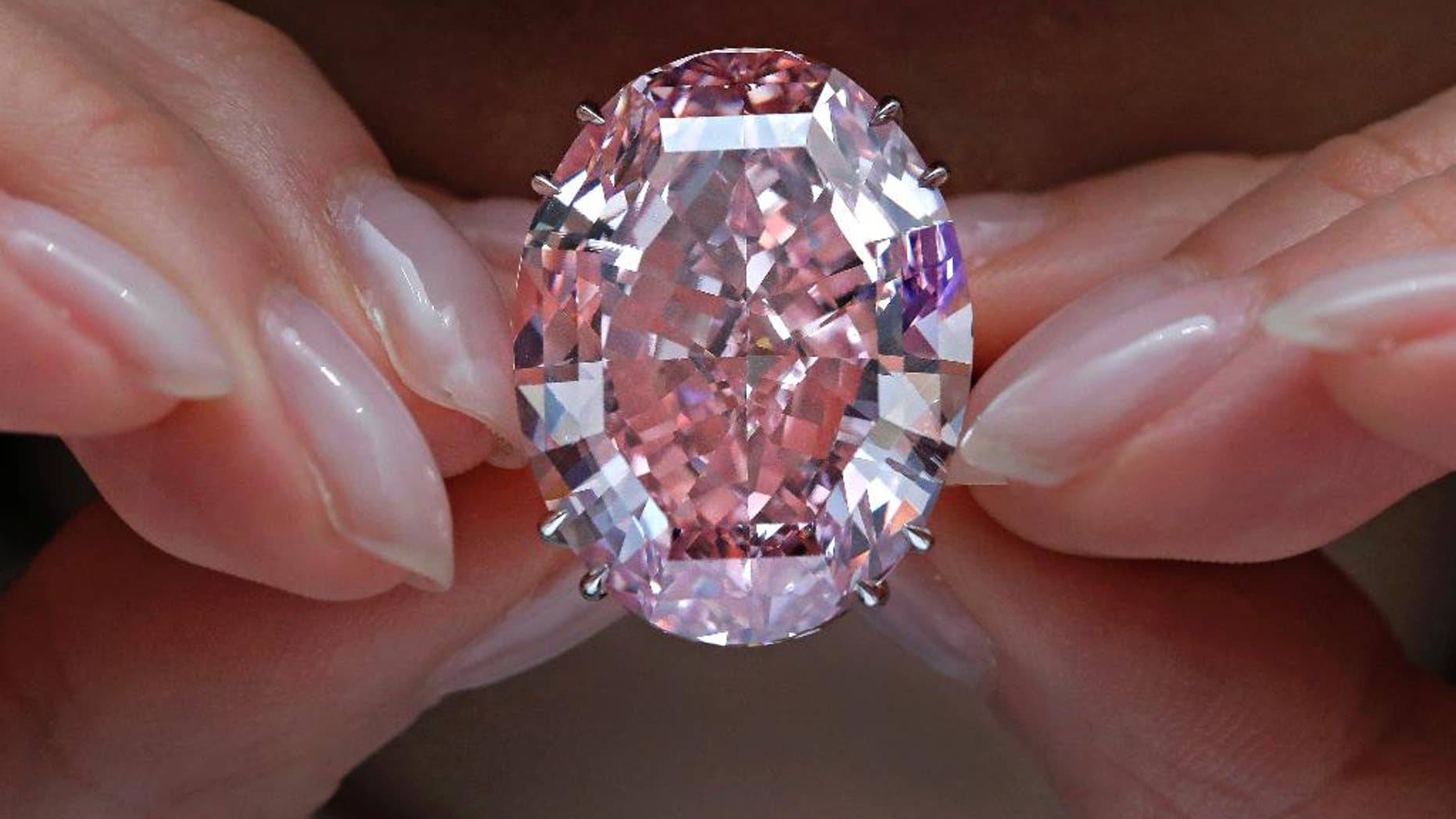 "FILE - In this Wednesday, March 29, 2017, file photo, the ""Pink Star"" diamond, the most valuable cut diamond ever offered at auction, is displayed by a model at a Sotheby's auction room in Hong Kong. The stunning 59.6 carat diamond has sold for HK$553 million or US$71.2 million at a Sotheby's auction in Hong Kong, setting a record for any diamond or jewel. It's Also the highest price for any work ever sold at auction in Asia. (AP Photo/Vincent Yu, File)"