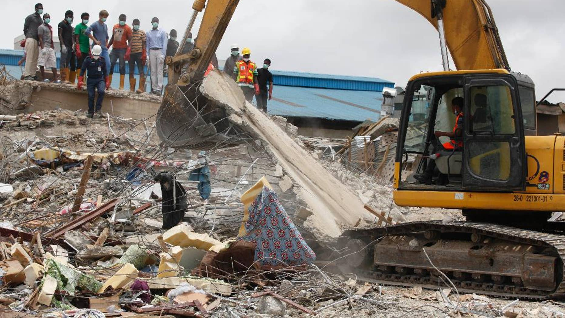 FILE - In this Wednesday, Sept. 17, 2014 file photo, rescue workers search for survivors in the rubble of a collapsed building belonging to the Synagogue Church of All Nations in Lagos, Nigeria. The Synagogue Church of All Nations of televangelist T. B. Joshua on Thursday, July 9, 2015 rejected a coroner's report recommending prosecution of the Nigerian church and two structural engineers in the collapse of a church building that killed 116 people, most of them visitors from South Africa. (AP Photo/Sunday Alamba, File)