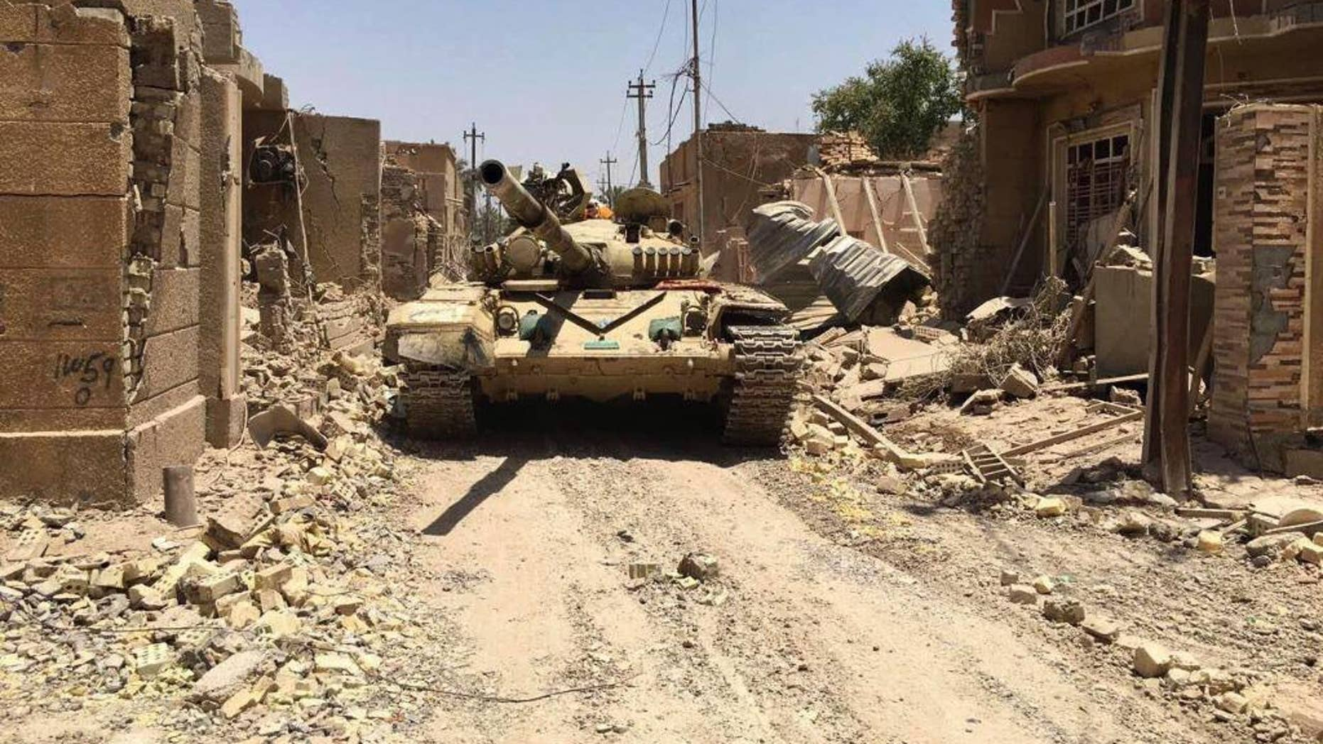 """Iraqi security forces in al-Julan neighborhood after defeating Islamic State militants in Fallujah, Iraq, Sunday, June 26, 2016. A senior Iraqi commander said the city of Fallujah was """"fully liberated"""" from Islamic State militants on Sunday, after a more than monthlong military operation. (AP Photo)"""
