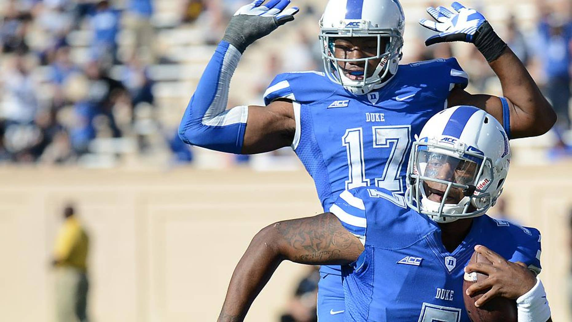 FILE - In this Oct. 18, 2014, file photo, Duke quarterback Anthony Boone (7) runs past Virginia's Brandon Phelps (21) for a first down during an NCAA college football game in Durham, N.C. Maybe Duke really wasn't a one-year wonder in 2013. (AP Photo/The Herald-Sun, Bernard Thomas, File)