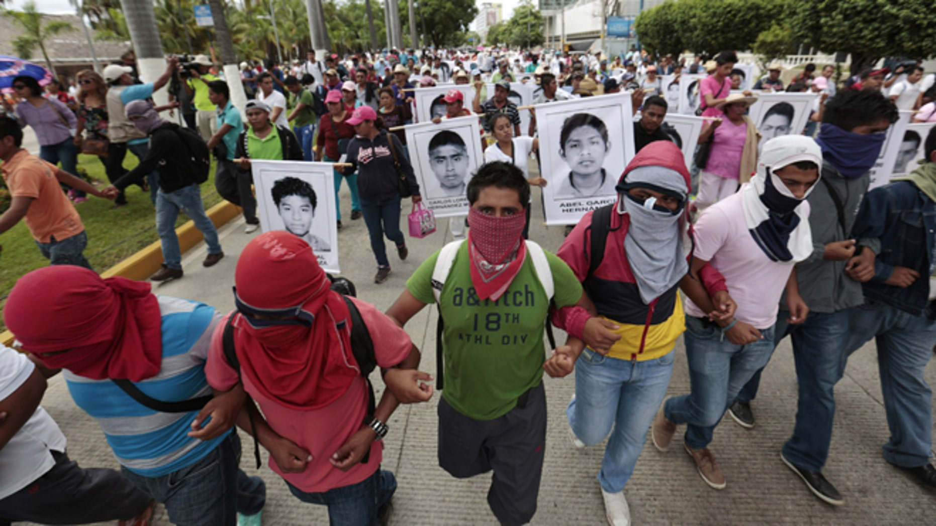Masked demonstrators march with photographs of missing students and chant slogans to protest the disappearance of 43 students from the Isidro Burgos rural teachers college in Acapulco, Guerrero state, Mexico, Friday, Oct. 17, 2014. Investigators determined that 28 sets of human remains recovered from a mass grave discovered outside Iguala, in Guerrero state, last weekend were not those of any of the youths who haven't been seen since being confronted by police in that city Sept. 26. (AP Photo/Eduardo Verdugo)