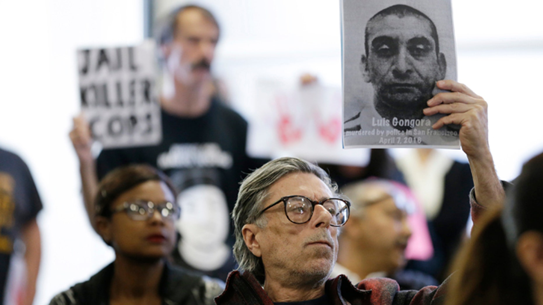 A man holds up a picture of Luis Gongora during a town hall meeting Wednesday, April 13, 2016, in San Francisco.