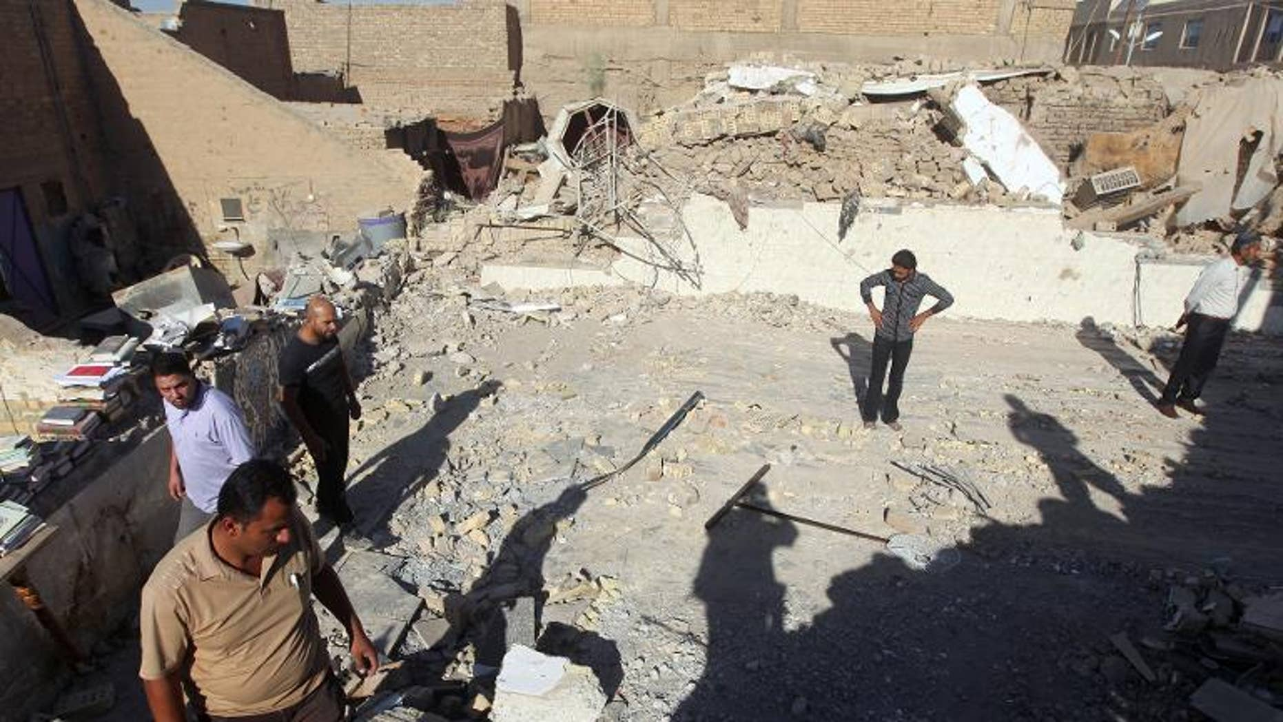 Iraqis inspect the scene following an explosion at the Al-Hussein mosque south of Baghdad, on September 30, 2013