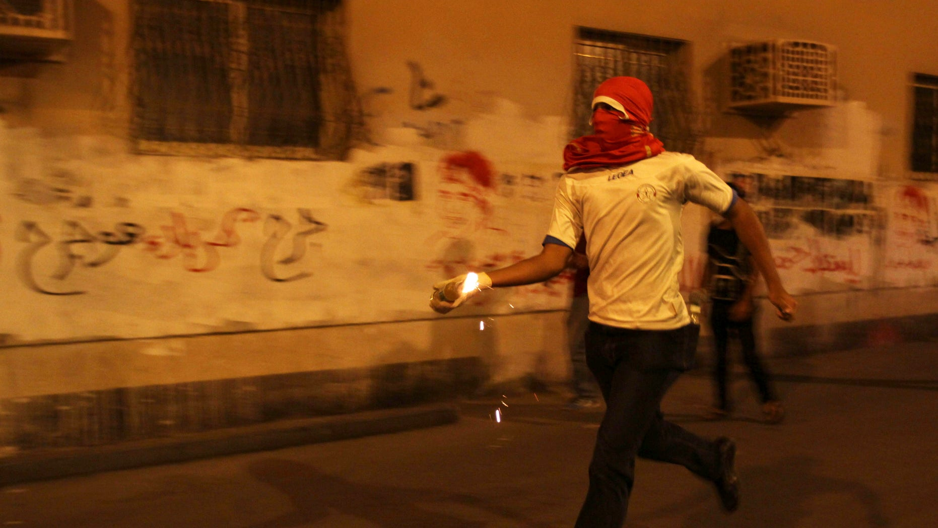 A Bahraini anti-government protester prepares to throw a petrol bomb at riot police during clashes following a rally protesting against the upcoming Formula One race in Sanabis, Bahrain, Tuesday, April 9, 2013. The Bahrain Grand Prix is to be held April 21. Bahrain says four suspects have been arrested after homemade firebombs were hurled at the foreign ministry in a possible escalation of anti-government protests. (AP Photo/Hasan Jamali)