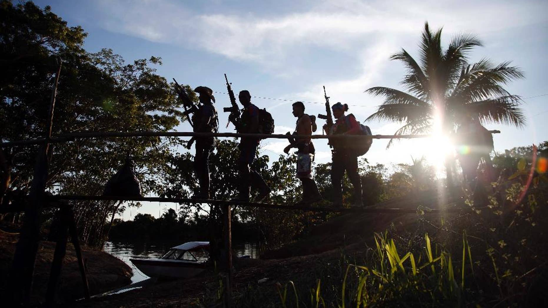 In this Aug. 12, 2016 photo, rebels of the 48th Front of the Revolutionary Armed Forces of Colombia walk on a makeshift footbridge in the southern jungles of Putumayo, Colombia. With the peace accords about to signed between the FARC and the governemt, gone are the days when they had to change camp every few days for fear of being stunned in their sleep by bombs falling from the skies.  (AP Photo/Fernando Vergara)