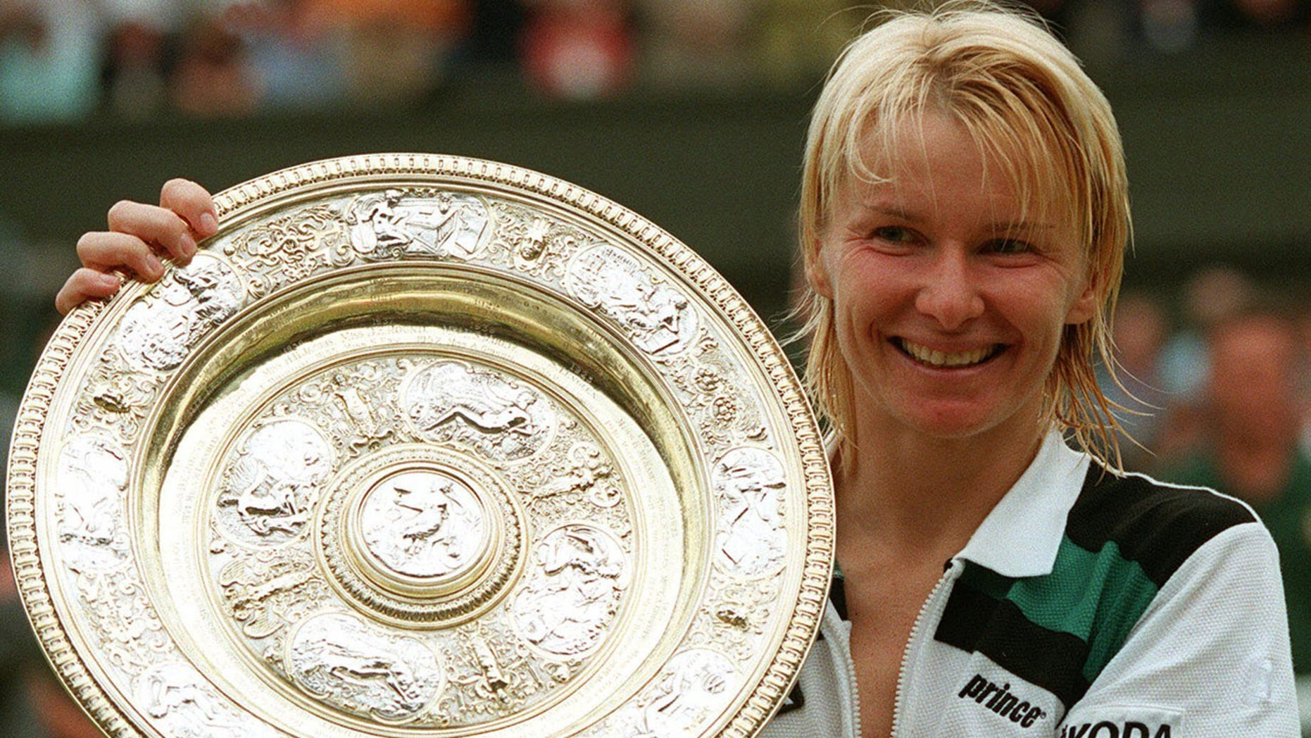 July 4, 1998 file photo, Jana Novotna, of the Czech Republic, displays the women's singles trophy after her victory over France's Nathalie Tauziat in the final on Wimbledon's Centre Court.