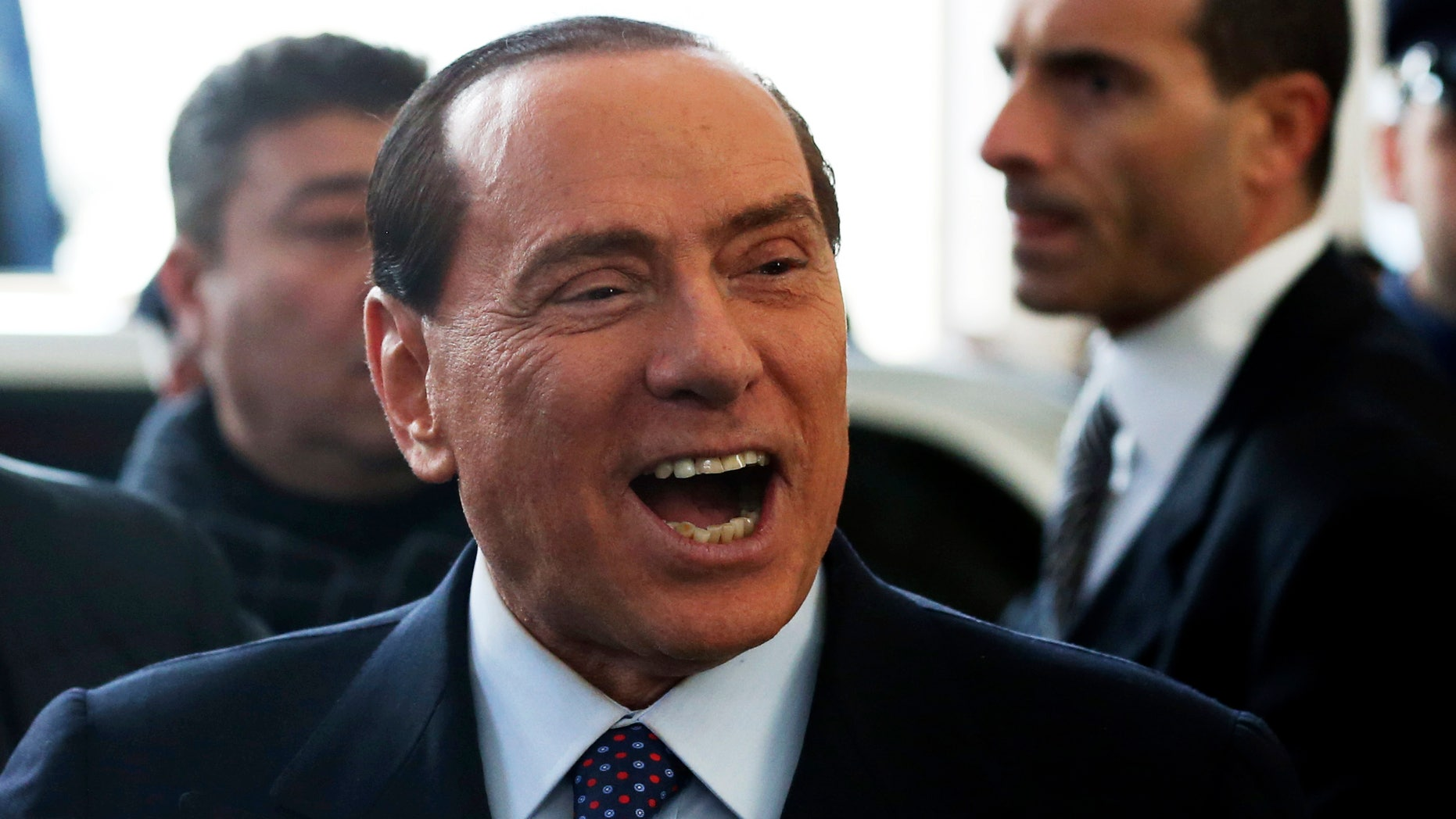 """Former Italian premier Silvio Berlusconi smiles as he arrives at Milan's central train station, Italy, Saturday, Dec. 29, 2012. Italian Premier Mario Monti announced Friday he is heading a new campaign coalition made of up centrists, business leaders and pro-Vatican forces who back his """"ethical"""" vision of politics, aiming for a second mandate in office if his fledging reform movement wins big in parliamentary elections. Monti was appointed premier 13 months ago after his scandal-plagued predecessor Silvio Berlusconi failed to stop Italy from sliding deeper into the eurozone debt crisis. He quit earlier this month after Berlusconi pulled his party's support from Monti's government, but is now continuing in a caretaker role until the next elections. (AP Photo/Luca Bruno)"""
