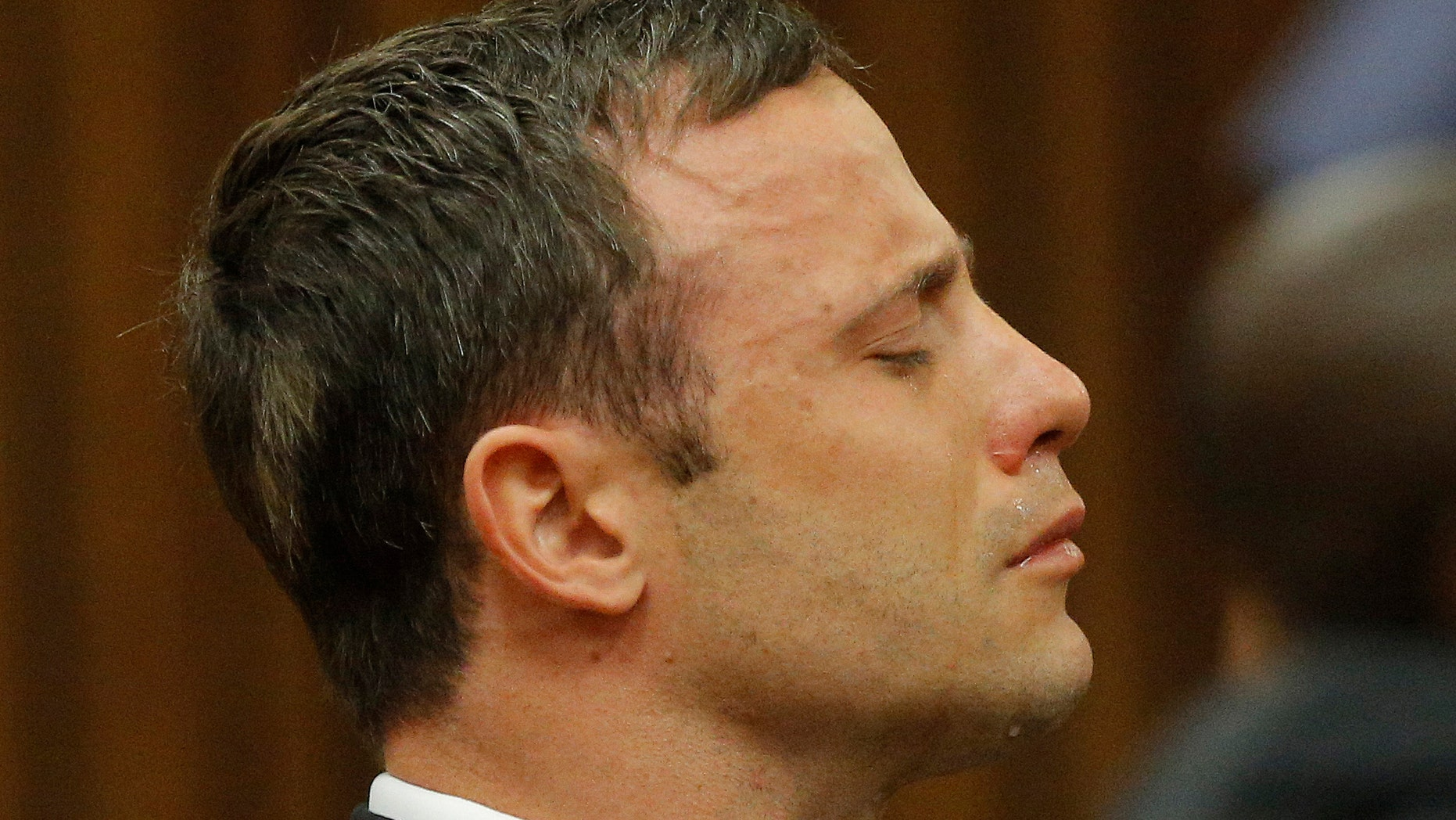 Oscar Pistorius reacts in the dock in Pretoria, South Africa, Thursday Sept. 11, 2014 as Judge Thokozile Masipa reads notes as she delivers her verdict in Pistorius' murder trial. The South African judge in Oscar Pistoriusâ murder trial said Thursday that prosecutors have not proved beyond a reasonable doubt that the double-amputee Olympic athlete is guilty of premeditated murder. (AP Photo/Kim Ludbrook, Pool)