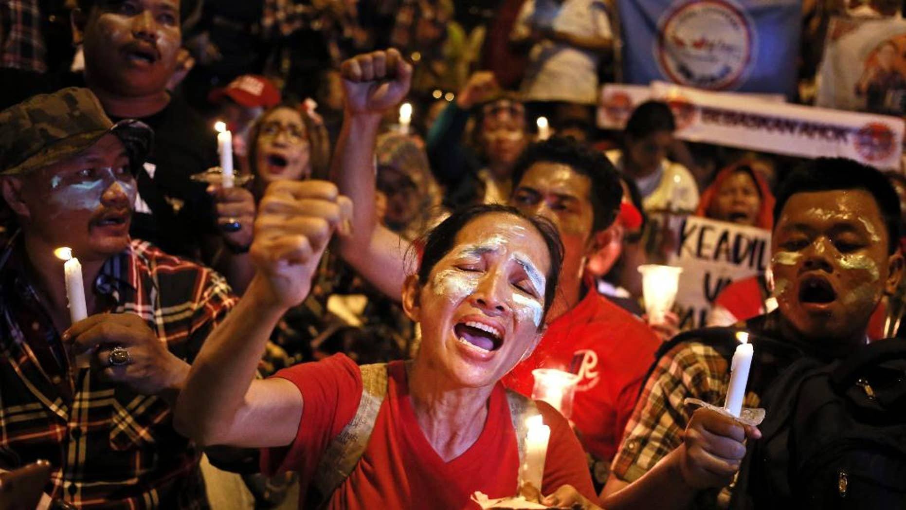 "Supporters of Jakarta Governor Basuki ""Ahok"" Tjahaja Purnama light candles and shout slogans during a rally outside Cipinang Prison where he is being held after a court sentenced him to two years in prison, in Jakarta, Indonesia, Tuesday, May 9, 2017. Judges handed down the verdict for the minority Christian governor on Tuesday for blaspheming the Quran, a jarring ruling that undermines the reputation of the world's largest Muslim nation for practicing a moderate form of Islam. (AP Photo/Dita Alangkara)"