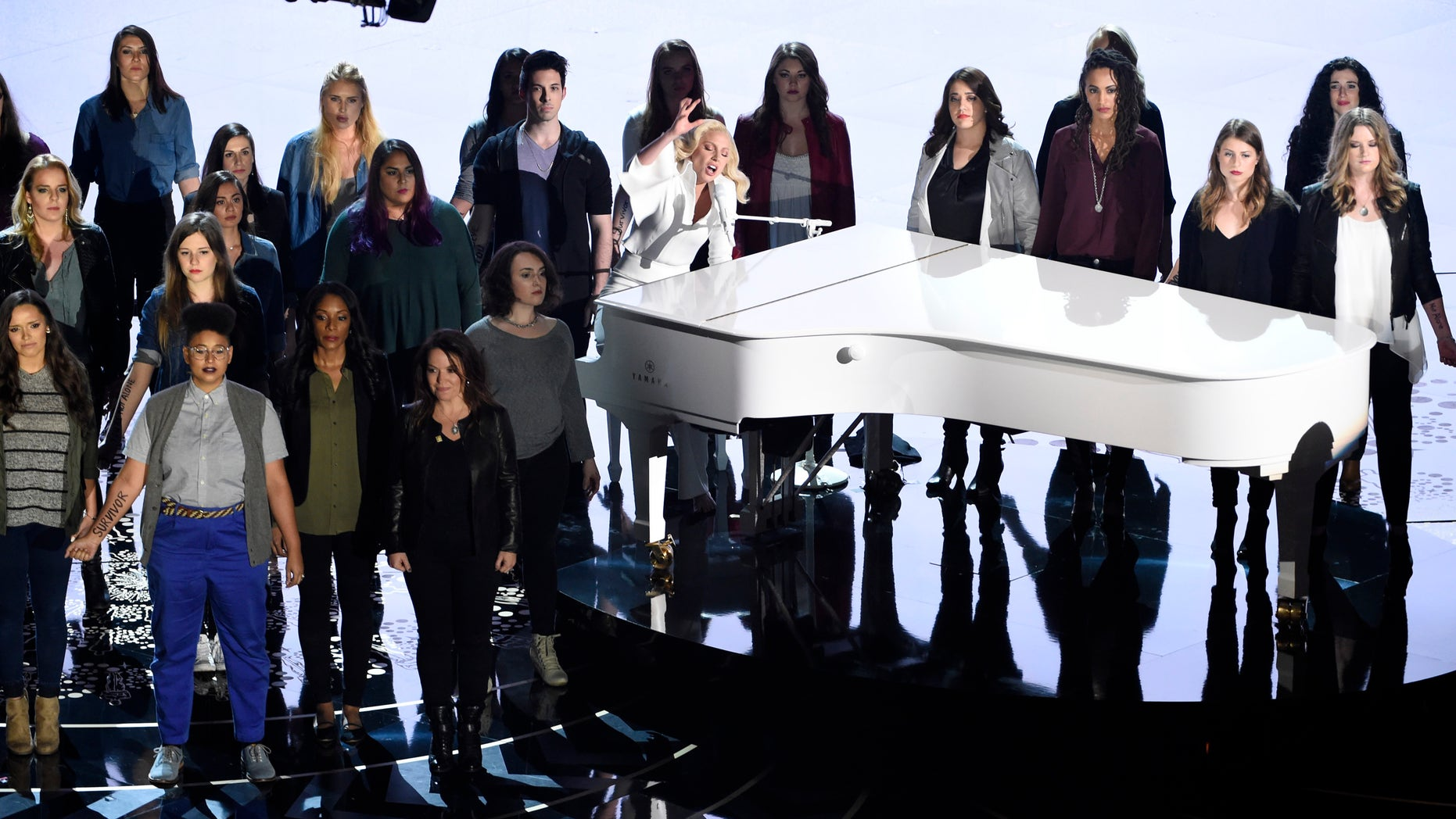 "Lady Gaga, center, performs ""Til It Happens To You"" that is nominated for best original song from ""The Hunting Ground"" on stage with survivors of abuse at the Oscars on Sunday, Feb. 28, 2016, at the Dolby Theatre in Los Angeles. (Photo by Chris Pizzello/Invision/AP)"