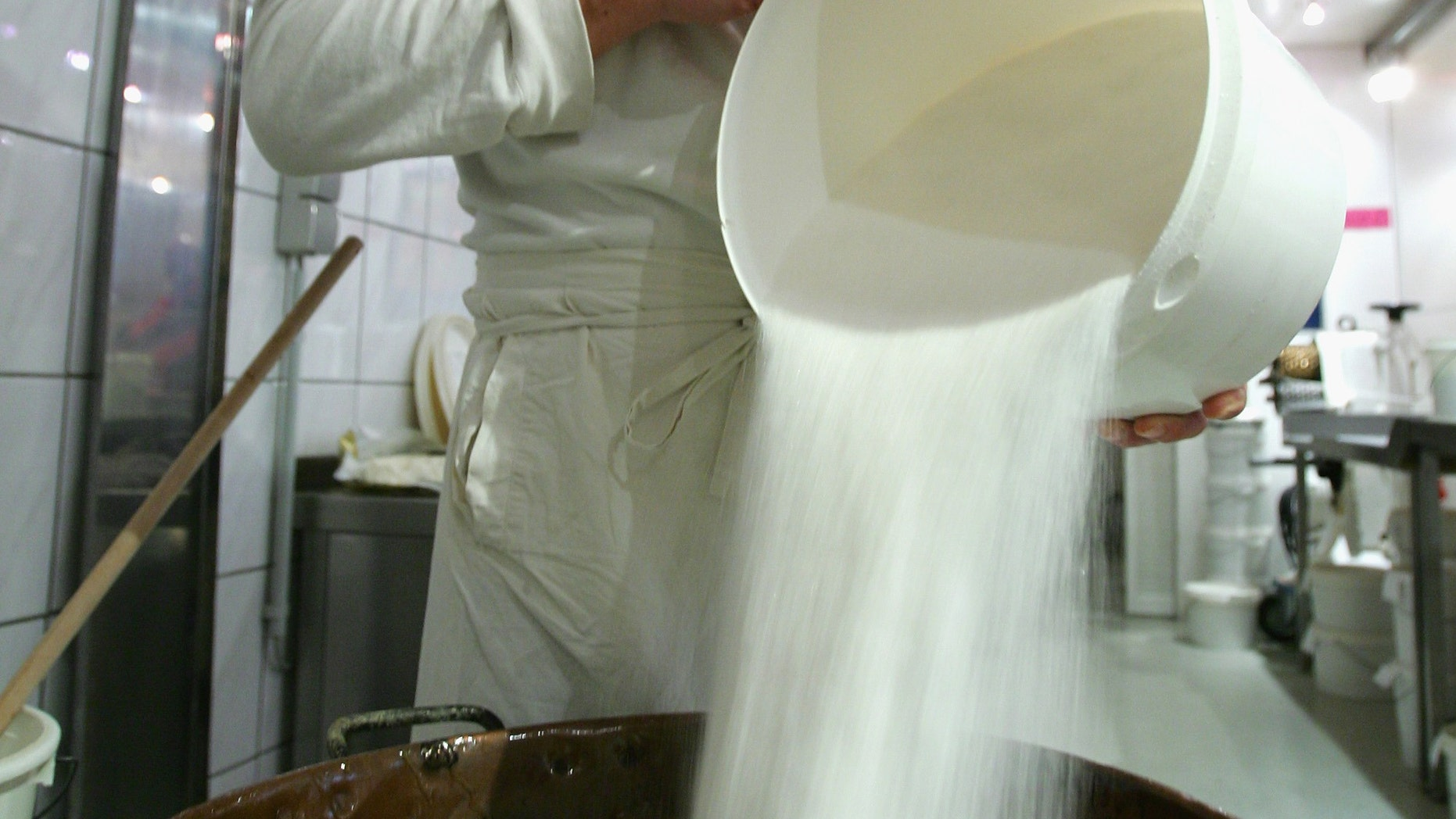 BERLIN - OCTOBER 12:  Hjalmar pours out sugar in a boiling pot on October 12, 2007 in Berlin, Germany. The Berlin based candy store produces 30 different kinds of handmade candies according traditional recipes.  (Photo by Andreas Rentz/Getty Images)
