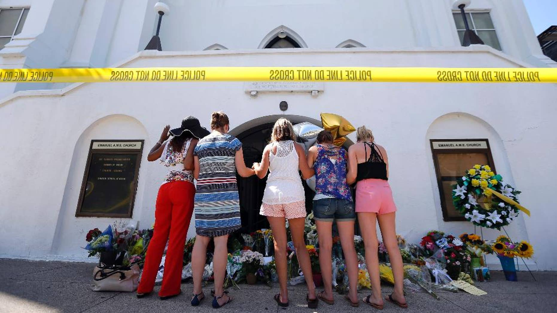 June 18, 2015: A group of women pray together at a makeshift memorial on the sidewalk in front of the Emanuel AME Church in Charleston, S.C.