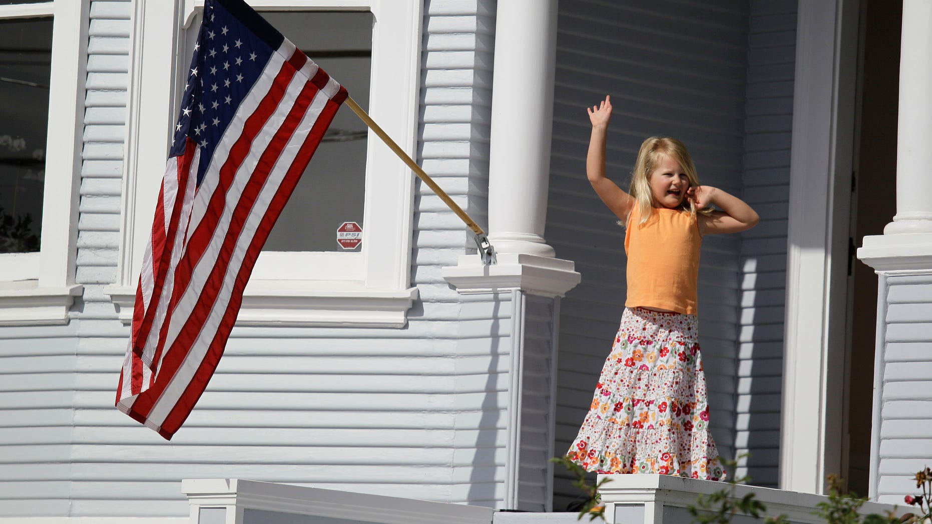 July 4, 2012: Margaret White, 5, waves from her porch as floats and marchers assemble for the start of the annual Fourth of July parade in Sausalito, Calif.