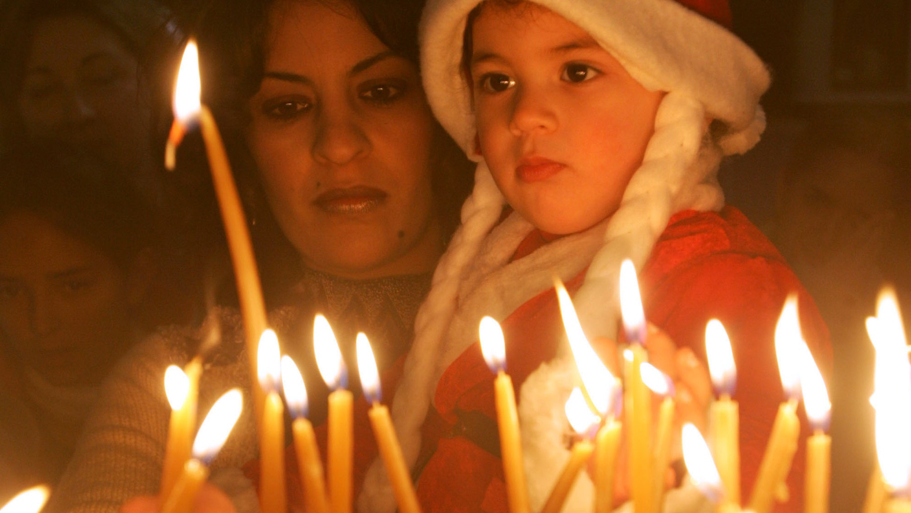 BETHLEHEM, WEST BANK - DECEMBER 24:  Iman Haddid and her 2-year-old daughter Dallah light votive candles at the Church of the Nativity December 24, 2004 in the biblical town of Bethlehem in the West Bank. A smaller crowd than in prevous years gathered in Manger Square for the start of the Christmas festivities at the traditional birthplace of Jesus with the local Palestinian governor blaming Israel for not easing security restrictions in time.  (Photo by David Silverman/Getty Images)