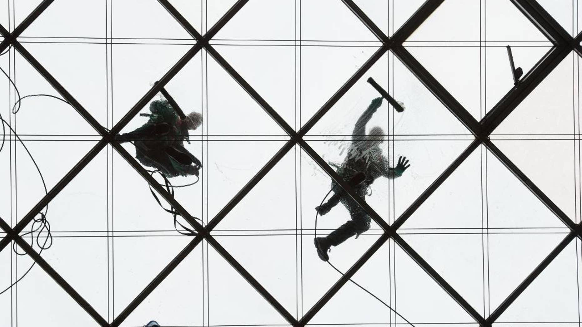 Two  window cleaners work on  the 27-meters-high glass ceiling of  a building in Dresden,Germany, Wednesday, March 30, 2016.  (Sebastian Kahnert/dpa via AP)