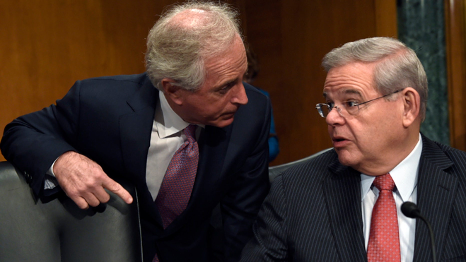 FILE - In this Jan. 27, 2015 file photo, Sen. Robert Menendez, D-N.J., right, and Sen. Bob Corker, R-Tenn. talk on Capitol Hill in Washington. A bipartisan bill in the Senate would set up a nonprofit foundation to help eliminate forced labor and sexual servitude around the world. The Senate Foreign Relations Committee is to vote Thursday on the bill introduced by chairman Sen. Bob Corker, R-Tenn., and Robert Menendez, D-N.J., the ranking Democrat on the committee.  (AP Photo/Susan Walsh, File)
