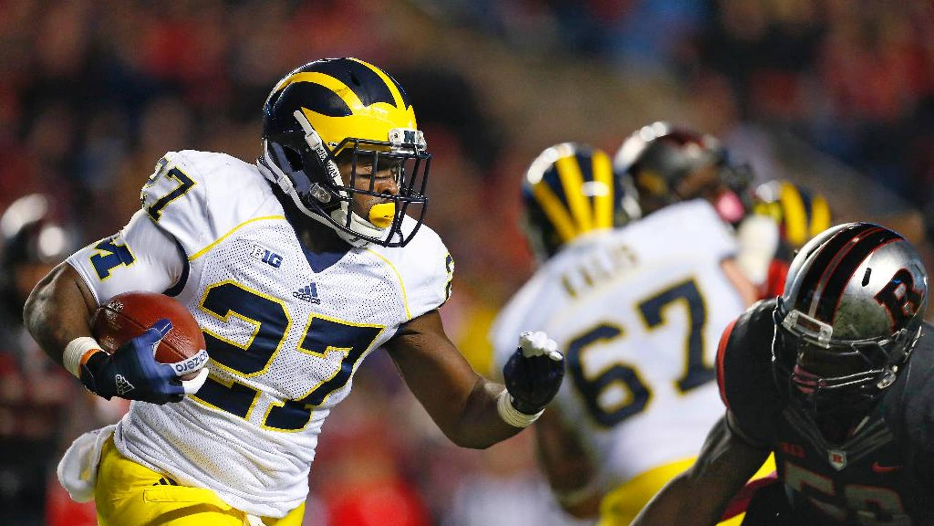 Michigan running back Derrick Green (27) is pursued by Rutgers' Quentin Gause during the second half of an NCAA college football game Saturday, Oct. 4, 2014, in Piscataway, N.J. Rutgers defeated Michigan 26-24. (AP Photo/Rich Schultz)