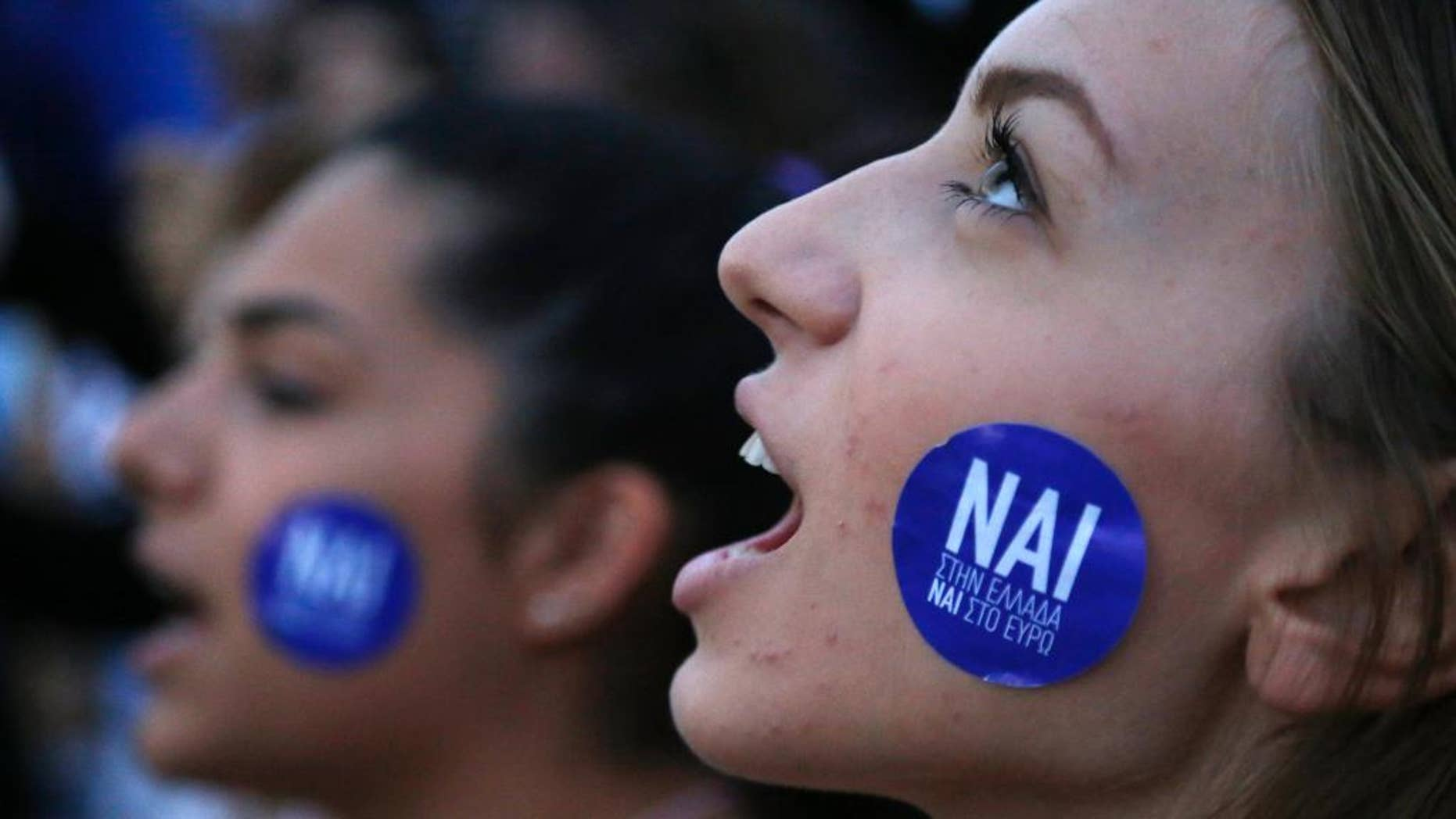 A demonstrator shouts slogans as the sticker on her cheek reading ''YES to Greece, Yes to Euro'' during a rally organized by supporters of the YES vote for the upcoming referendum in front of the Greek Parliament in Athens, Tuesday, June 30, 2015 Greece's European creditors were assessing a last-minute proposal Athens made for a new two-year rescue deal, submitted just hours before the country's international bailout program expires and it loses access to billions of euros in funds. (AP Photo/Petros Karadjias)