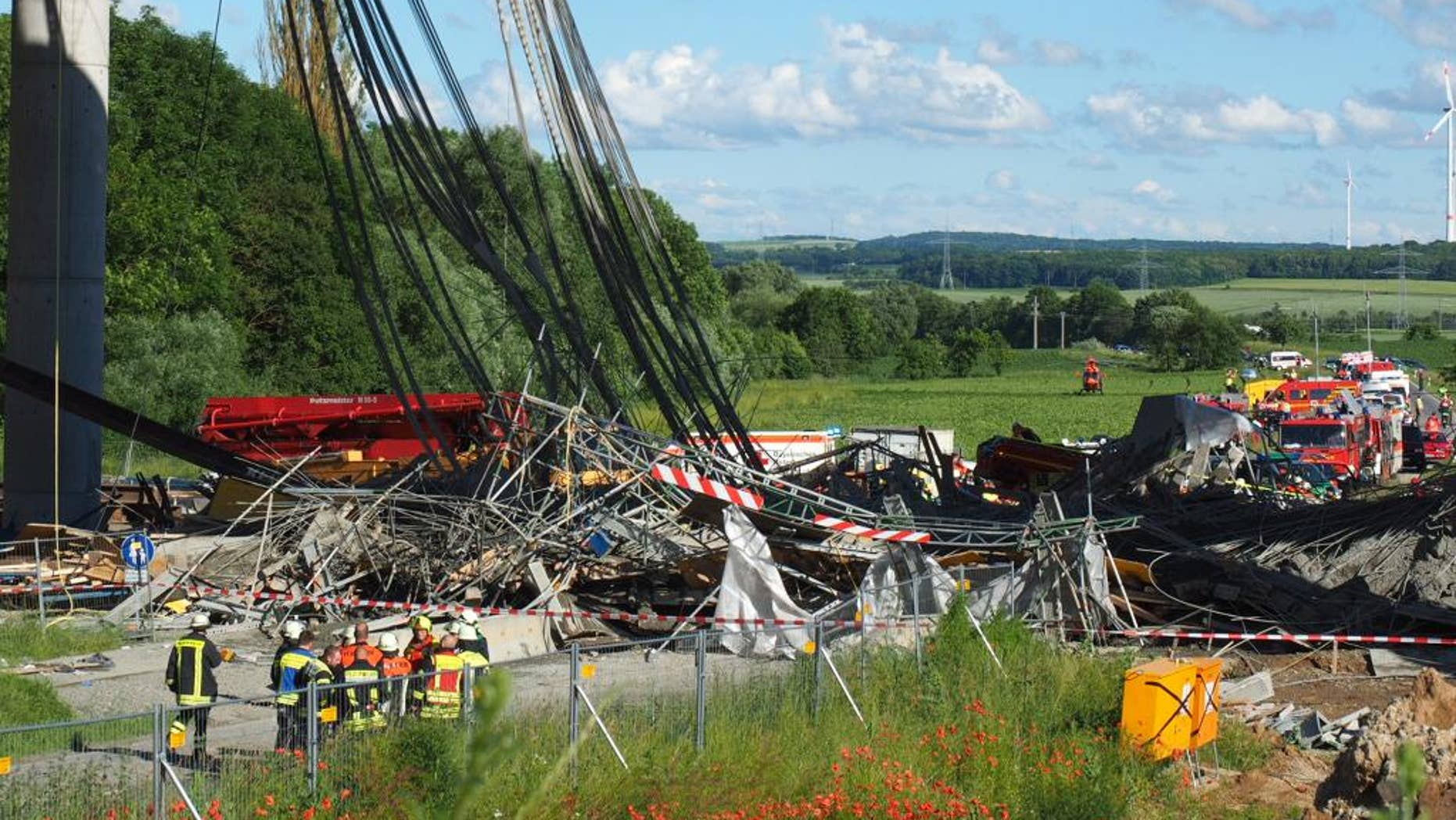 Firefighters stand near a collapsed scaffolding  at a highway bridge near Werneck northern Bavaria, Germany Wednesday June 15, 2016. German news agency dpa  is reporting that the scaffolding has collapsed on a highway bridge that was under construction in southern Germany.  ( Nicolas Armer/dpa via AP)