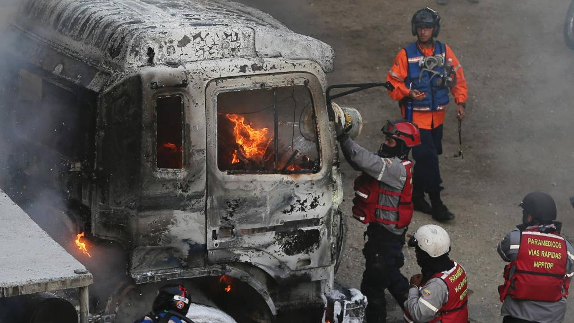 Fire-fighters put out a truck set on fire during anti-government protests in Caracas, Venezuela, Monday, April 24, 2017. Thousands of protesters shut down the capital city's main highway to express their disgust with the socialist administration of President Nicolas Maduro. Protesters in least a dozen other cities also staged sit-ins as the protest movement is entering its fourth week. (AP Photo/Fernando Llano)