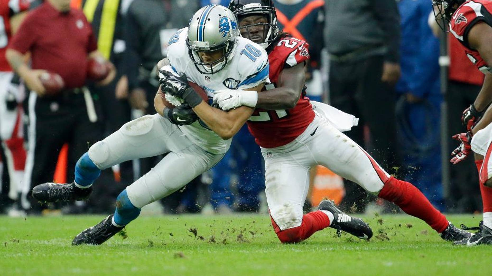 Atlanta Falcons cornerback Desmond Trufant (21) tackles Detroit Lions wide receiver Corey Fuller (10) in the second half of the NFL football game at Wembley Stadium, London, Sunday, Oct. 26, 2014.  (AP Photo/Matt Dunham)