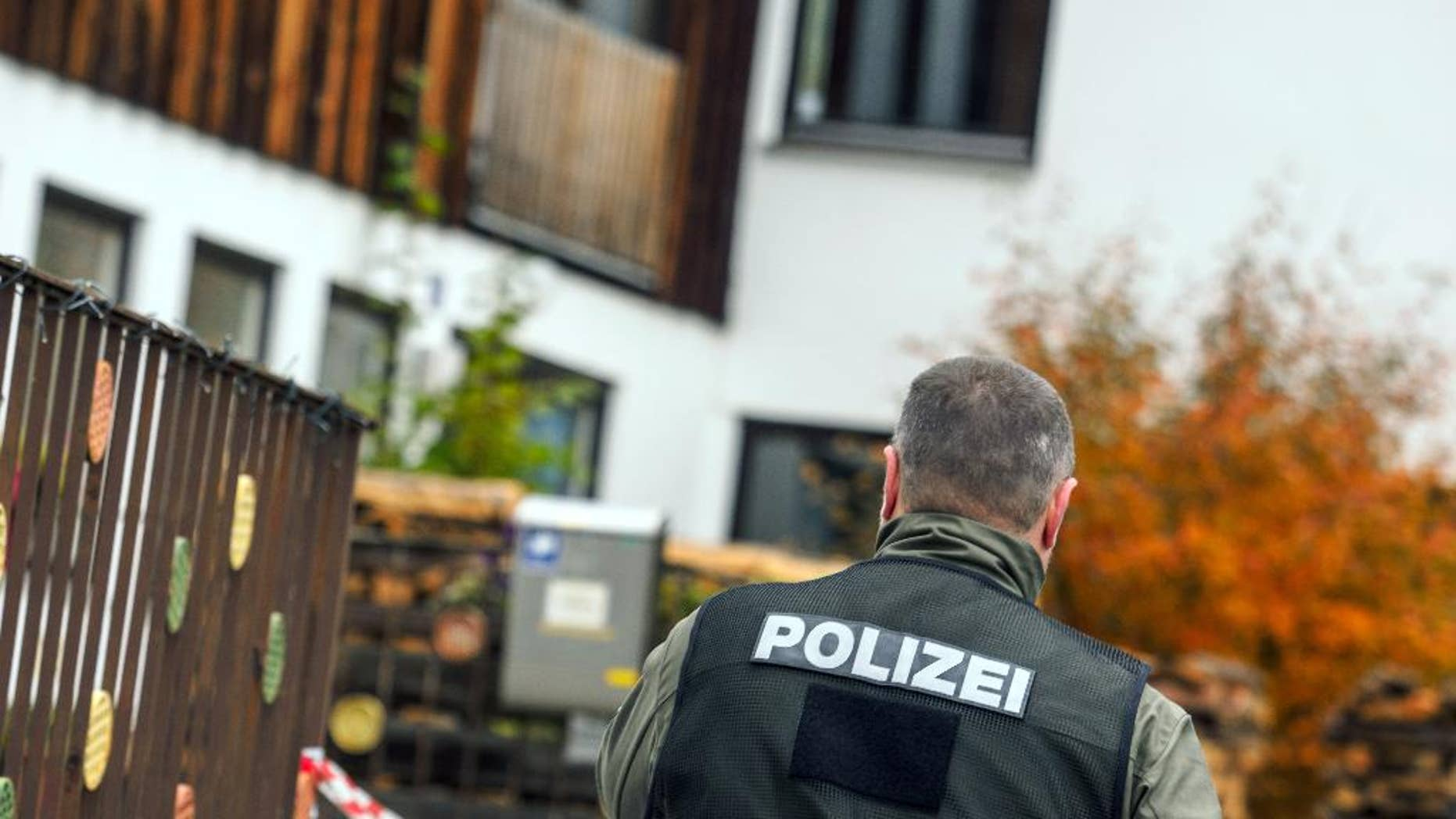 A policeman walks along the house in Georgensgmuend, Germany, Wednesday, Oct. 19, 2016, where an anti-government extremist opened fire on police in southern Germany during a raid in the morning in which they had planned to confiscate his weapons, and four officers were wounded, authorities said. The 49-year-old German man had legally possessed more than 30 weapons for hunting, but local authorities had revoked his license because he appeared increasingly unreliable, Bavarian Interior Minister Joachim Herrmann said. (Nicolas Armer/dpa via AP)