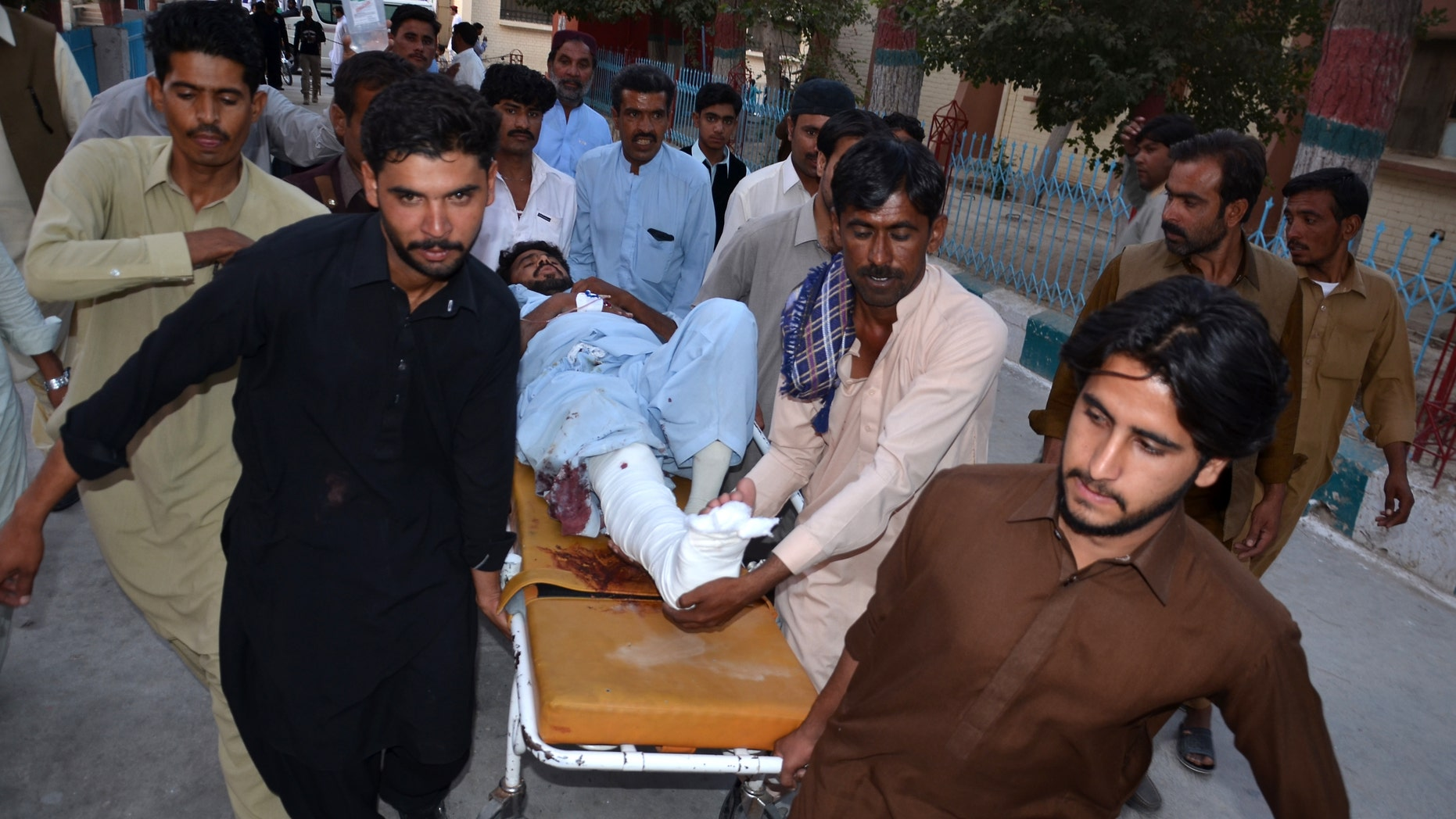 People rush an injured person to a hospital after a bomb blast in Pakistan.