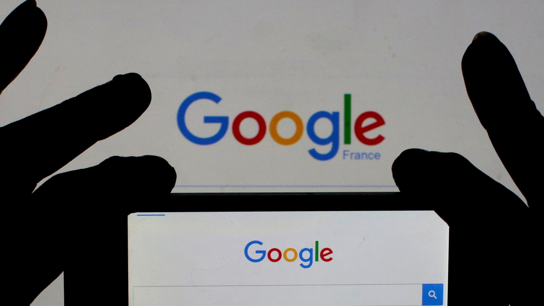 A woman holds her smart phone which displays the Google home page, in this picture illustration taken February 24, 2016. (REUTERS/Eric Gaillard/Illustration/Files)