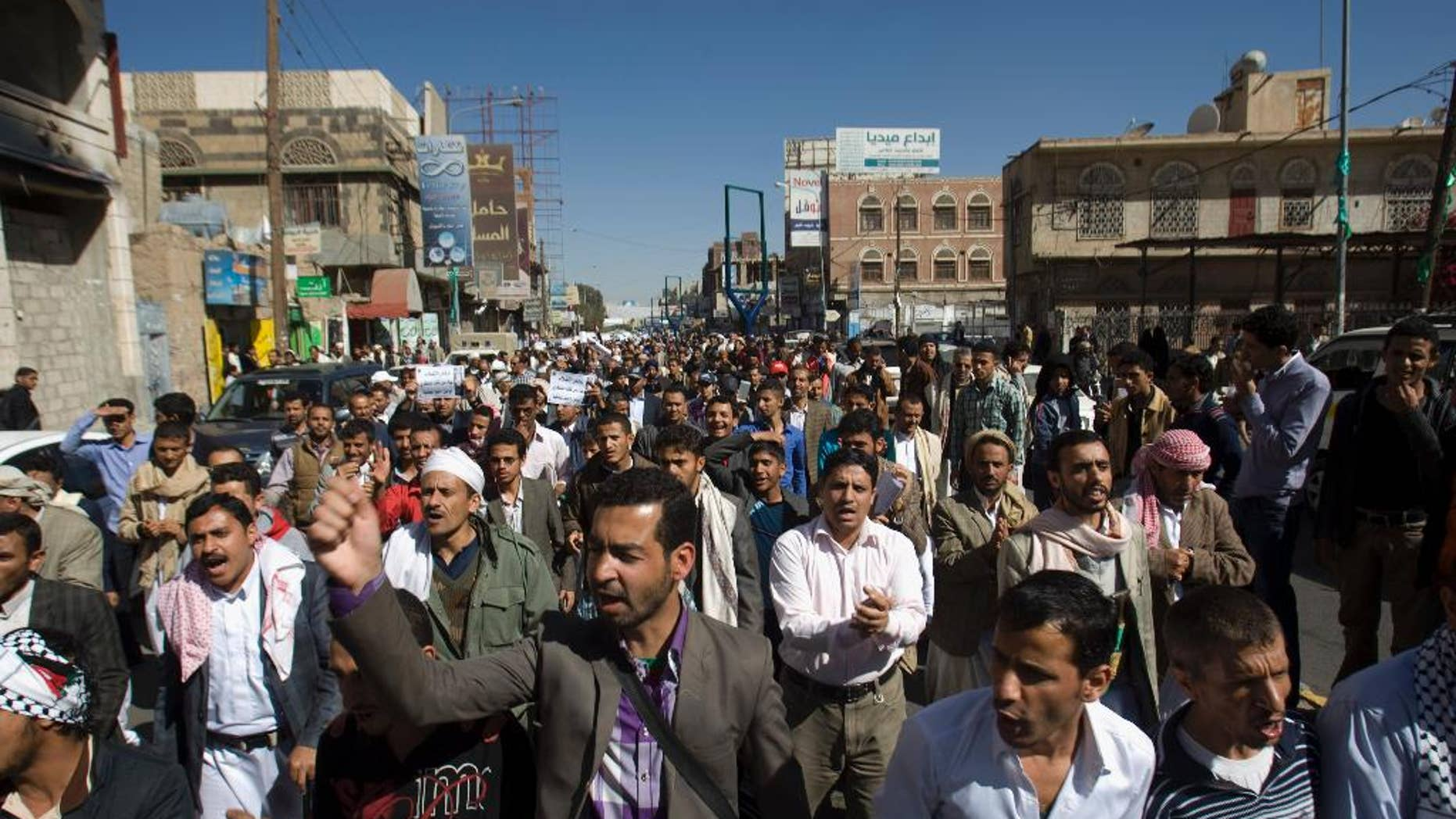 FILE - In this Saturday, Jan. 24, 2015 file photo, protesters chant slogans against Houthi Shiite rebels who hold the capital, Sanna, amid a power vacuum as they march on a street in Sanaa. A U.S. drone strike targeting al-Qaida in Yemen signals Washington's determination to keep fighting the militants despite political paralysis brought on by the minority Shiite power grab. But officials say an effective ground strategy to truly uproot the militants will have to await the emergence of a functioning local government that can act as an ally. (AP Photo/Hani Mohammed, File)