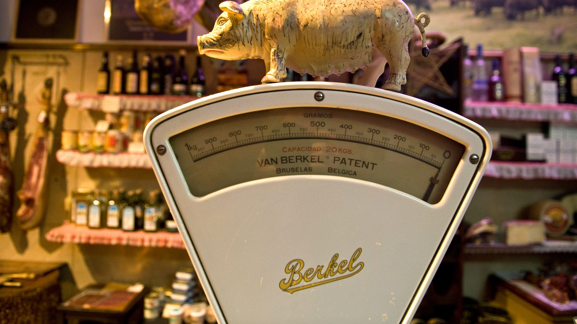 MADRID, SPAIN - DECEMBER 14: A small figurine of an Iberian Pig sits on an old weighing scales at the Alberto Lopez Araque jamon Iberico shop on December 14, 2012 in Madrid, Spain. Dry-cured Iberian ham or Jamon Iberico is a favourite amongst Spaniards and producers are hoping for improved sales over the busy christmas period. The jamon Iberico de Bellota are usually dry-cured for up to three years after the pigs have been few on a diet of acorns in the last three months of their lives.  (Photo by Denis Doyle/Getty Images)