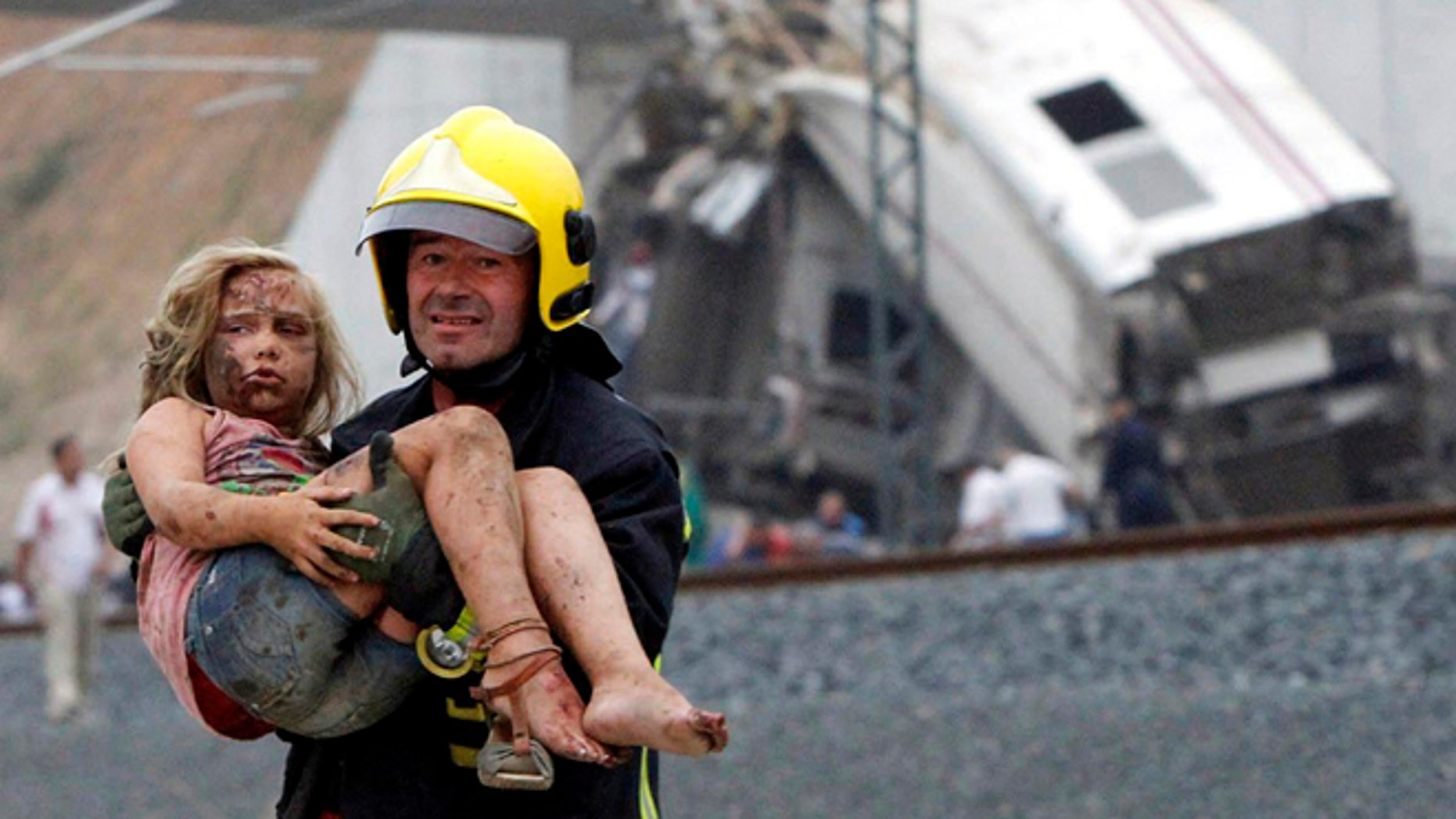 A fireman carries a wounded victim from the wreckage of a train crash near Santiago de Compostela, northwestern Spain.