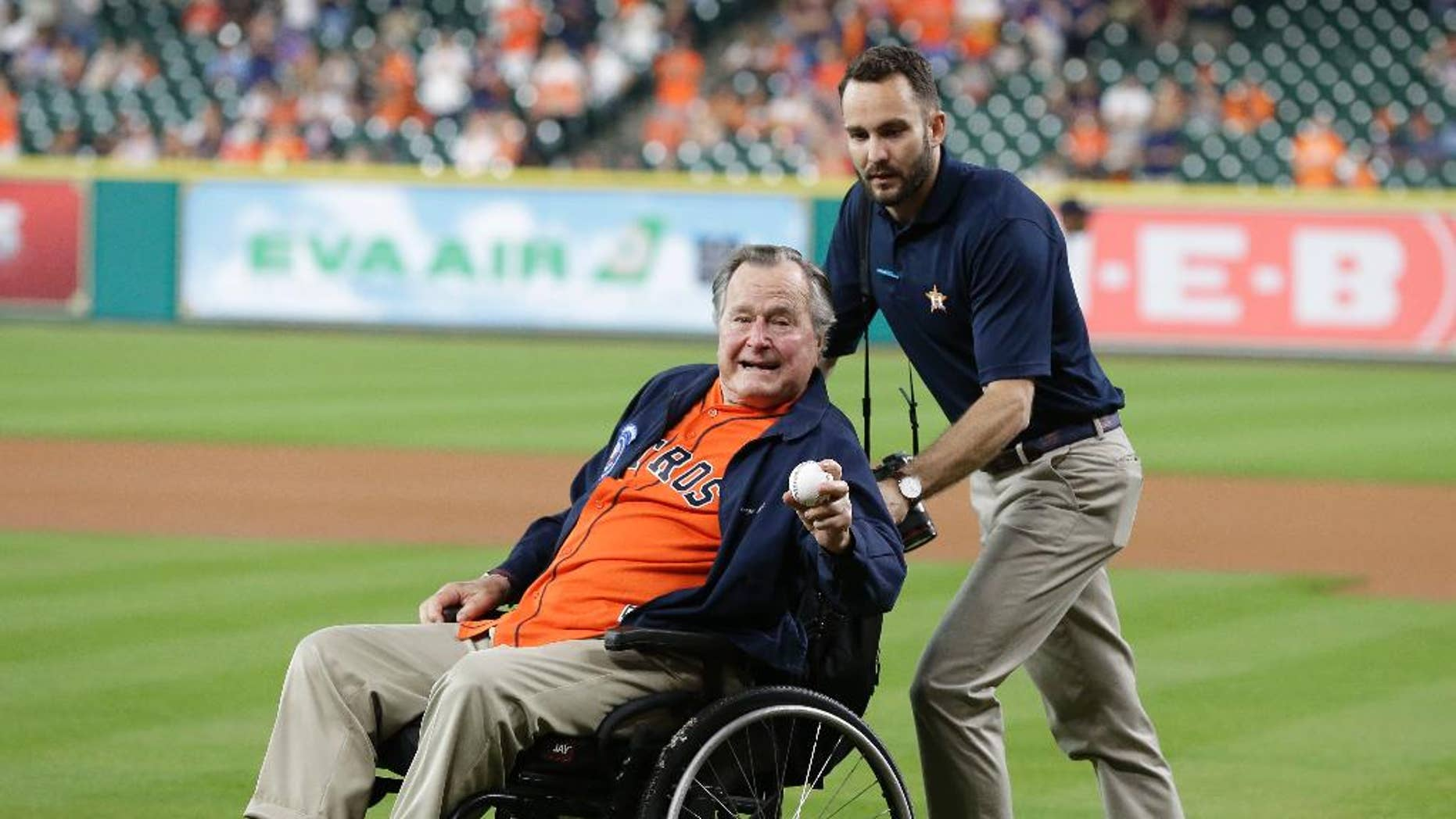 FILE - In this April 12, 2016 file photo, former President George H.W. Bush, left, shows his pitching grip as he wheeled out to the field to throw out the ceremonial first pitch to Houston Astros starting pitcher Collin McHugh before the baseball game against the Kansas City Royals in Houston. Fresh from his 92nd birthday, former President George H.W. Bush is enjoying himself in Maine after recovering from a fall at his home nearly a year ago. Bush led a group of 40 wounded warriors on a fishing trip at the helm of his speedboat Wednesday, June 15, 2016, three days after a low-key birthday celebration. (AP Photo/Pat Sullivan, File)