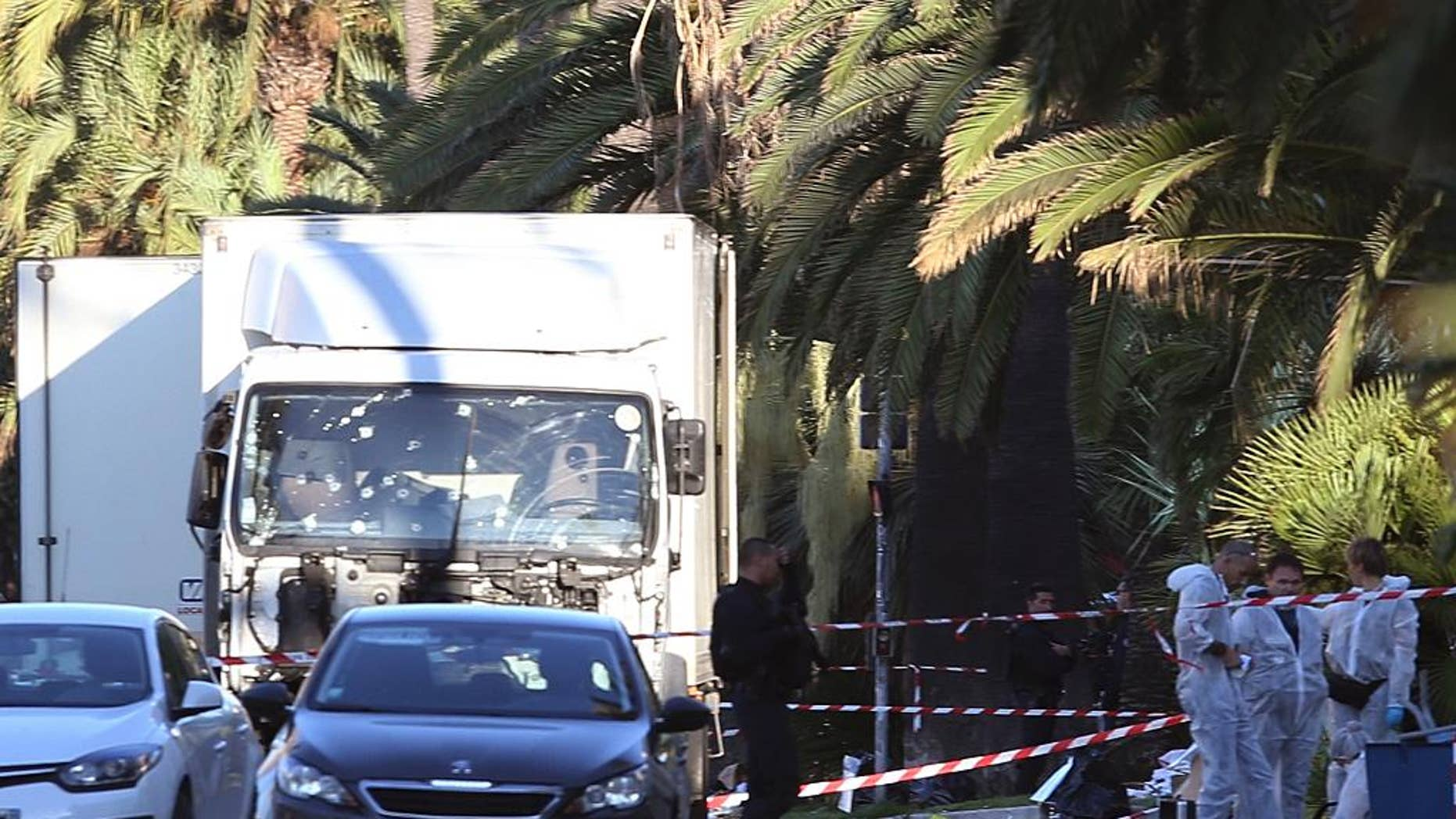 The truck which slammed into revelers late Thursday, July 14, is seen near the site of an attack in the French resort city of Nice, southern France, Friday, July 15, 2016.  France has been stunned again as a large white truck mowed through a crowd of revelers gathered for a Bastille Day fireworks display in the Riviera city of Nice. (AP Photo/Luca Bruno)