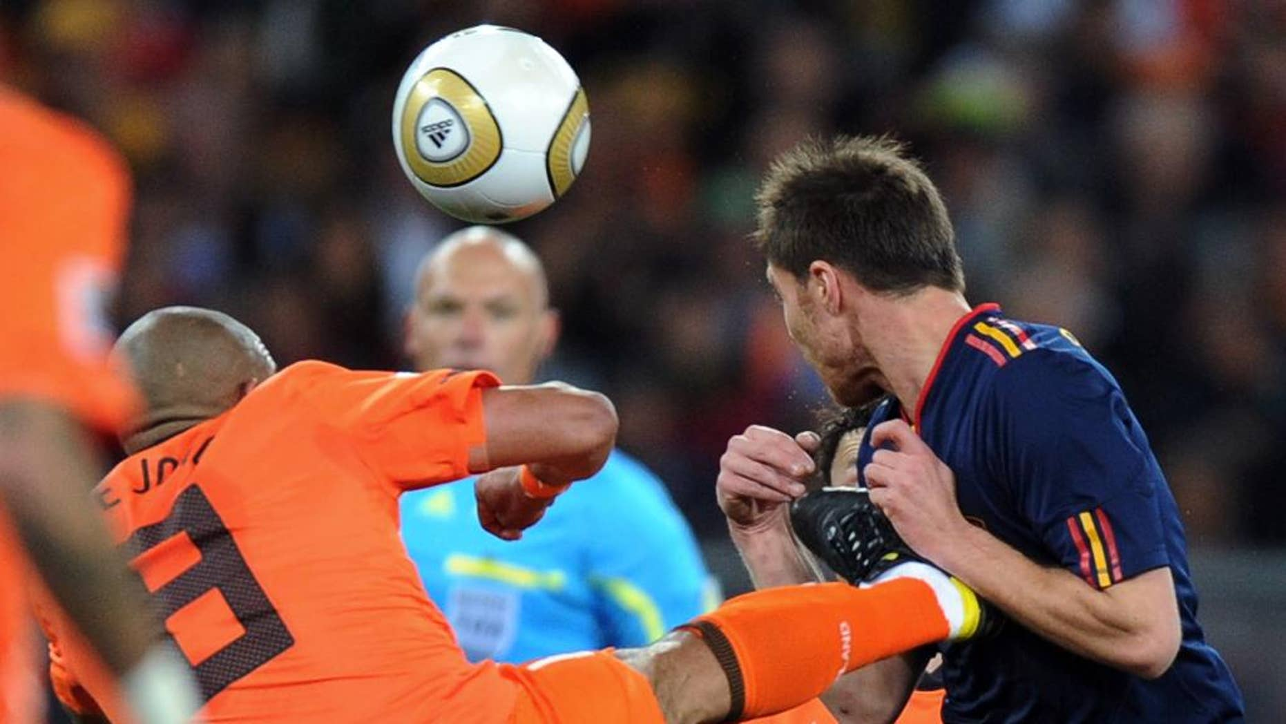 """FILE - In this Sunday, July 11, 2010 file photo, Netherlands' Nigel de Jong, left, fouls Spain's Xabi Alonso during the World Cup final soccer match between the Netherlands and Spain at Soccer City in Johannesburg, South Africa. The days of fluent, attacking """"total football"""" are long gone for the Netherlands. Now, results matter more than the way they are achieved. Anybody expecting the Netherlands to revert to the type of free-flowing attacking play that was long the hallmark of Orange teams when Louis van Gaal's team takes on Spain on Friday should think again. Van Gaal has signaled he will likely play five defenders against Spain to stifle the defending world champion's own fluent attacking style. That could revive memories of the brutal 2010 final in which eight Dutch players were booked and one sent off. Robin van Persie said Sunday he has no regrets about the 2010 campaign.""""I think we can look back with pride"""" at 2010, he says.  (AP Photo/Daniel Ochoa de Olza, file)"""