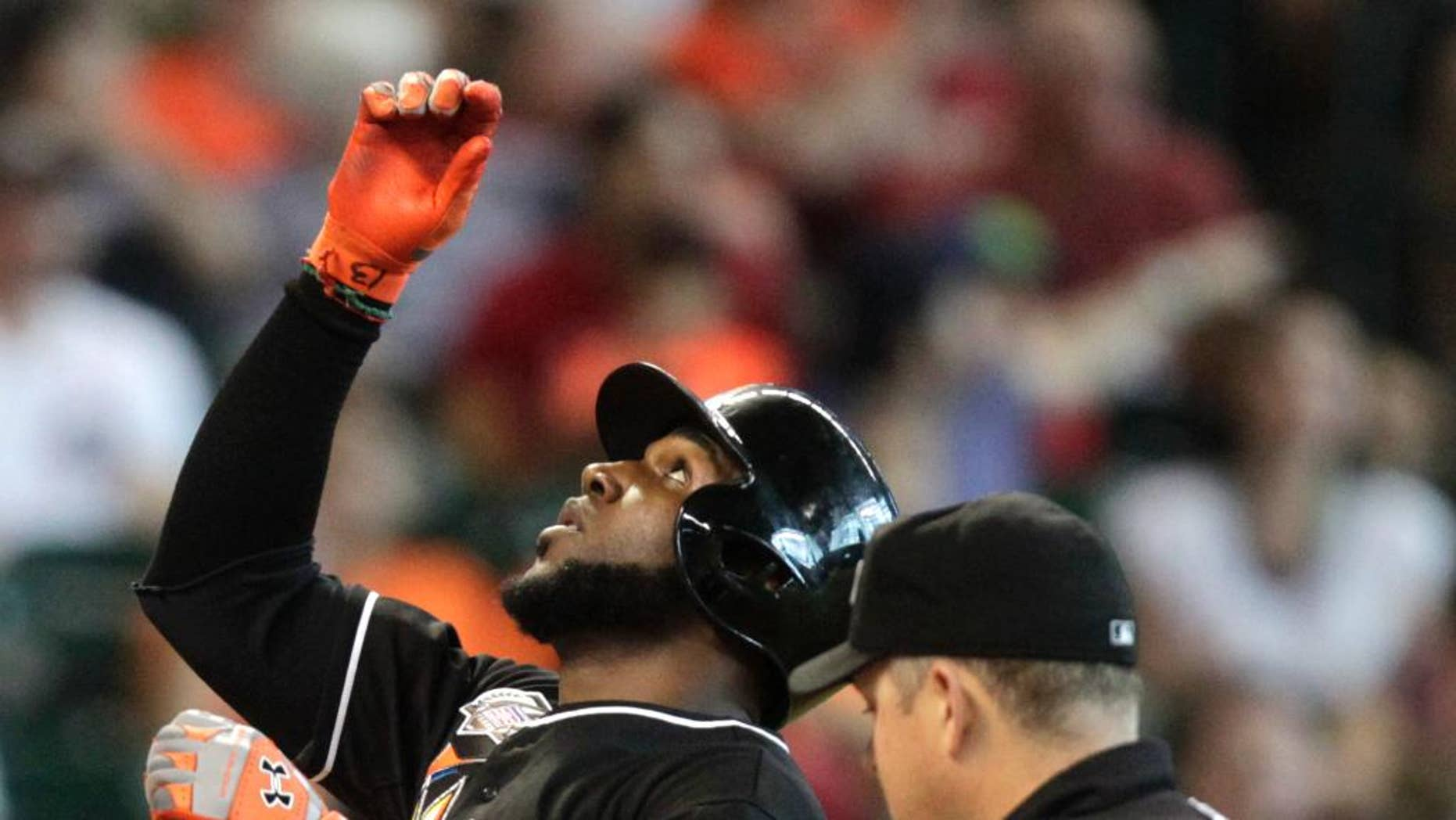 Miami Marlins Marcell Ozuna points to the sky while crossing home plate after hitting a home run during the sixth inning of a baseball game against the Houston Astros, Sunday, July 27, 2014, in Houston. (AP Photo/Patric Schneider)