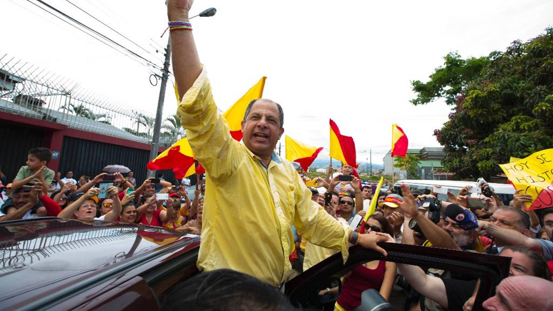 Luis Guillermo Solis, presidential candidate for the Citizen's Action Party, waves to supporters after casting his vote in the presidential runoff election in San Jose, Costa Rica, Sunday, April 6, 2014. Solis' only rival in the runoff dropped out of the race last month, leaving Solis one remaining challenge: getting enough Costa Ricans to the polls to give him a respectable vote total. (AP Photo/Moises Castillo)