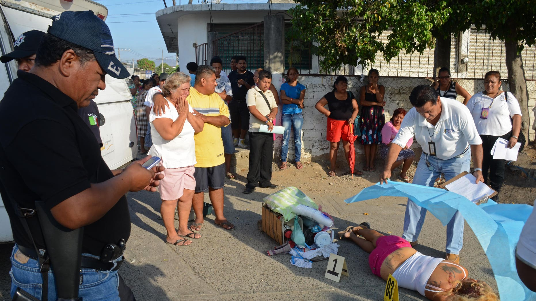 A forensic worker covers the body of a woman who was shot dead by assailants, whose daughter was also killed, while she was selling coffee on a street corner in Acapulco, Mexico, Tuesday, April 9, 2013. Violence, kidnappings and extortions carried out by drug cartels continue to plague this Pacific resort city which has witnessed a large increase in violent crimes during the past years. (AP Photo/Bernandino Hernandez)