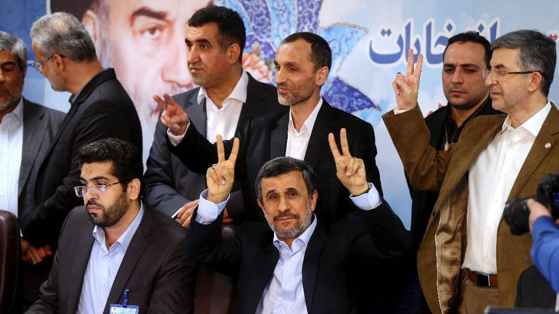 Former Iranian President Mahmoud Ahmadinejad, seated center, flashes the victory sign as he is registering candidacy for the upcoming presidential elections at the Interior Ministry in Tehran, Iran, Wednesday, April 12, 2017. Ahmadinejad on Wednesday unexpectedly filed to run in the country's May presidential election, contradicting a recommendation from the supreme leader to stay out of the race. (AP Photo/Ebrahim Noroozi)
