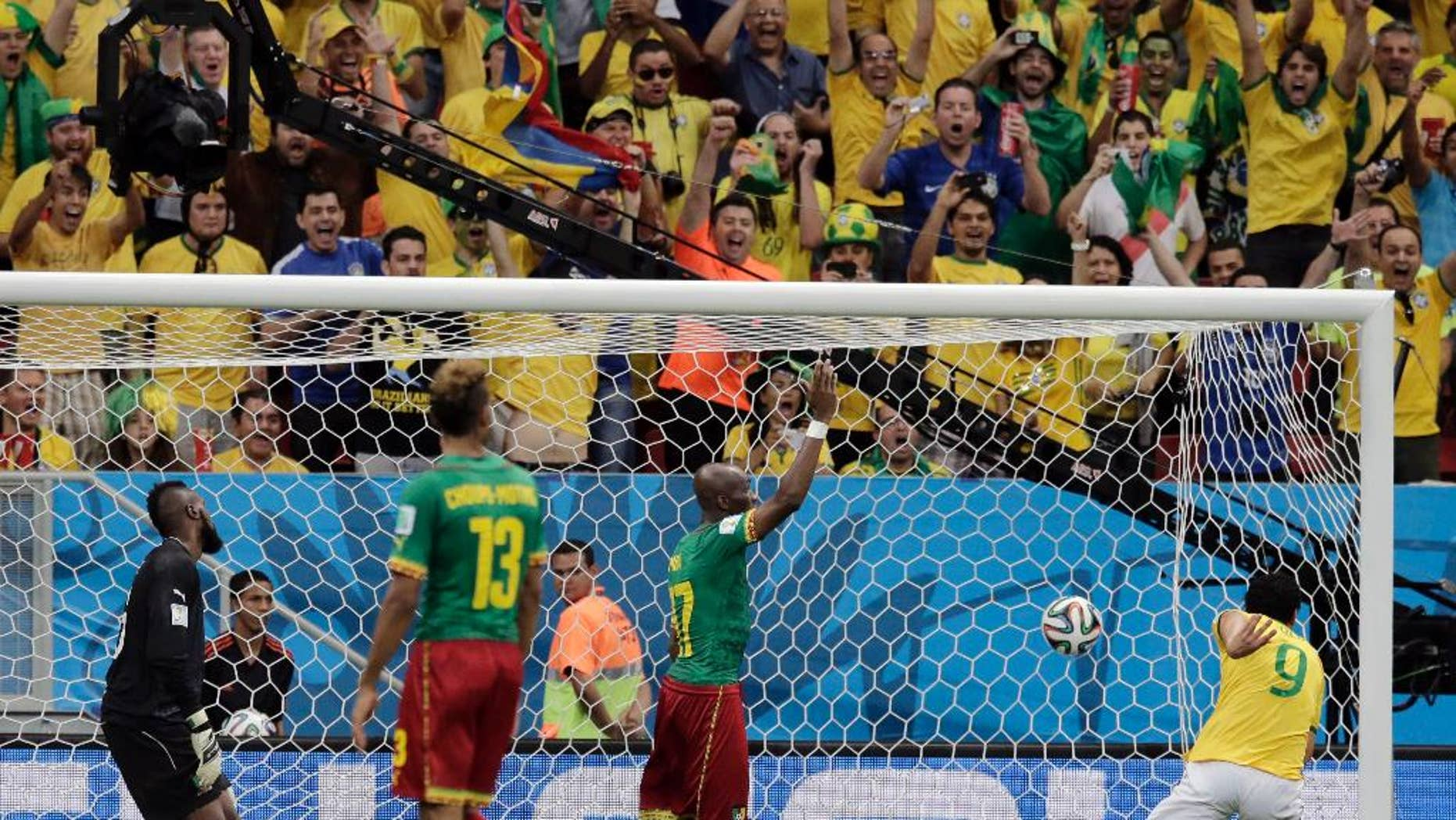 Spectators cheer as Brazil's Fred (9) scores his side's third goal against Cameroon's goalkeeper Charles Itandje during the group A World Cup soccer match between Cameroon and Brazil at the Estadio Nacional in Brasilia, Brazil, Monday, June 23, 2014. (AP Photo/Bernat Armangue)