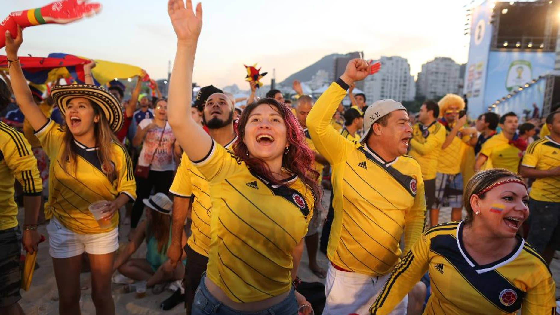Colombia soccer fans celebrate the goal scored by their team as they watch a live telecast of their team's World Cup match with Japan inside the FIFA Fan Fest area on Copacabana beach, in Rio de Janeiro, Brazil, Tuesday, June 24, 2014. After 12 days of competition, Colombia has already reached the second round with a game to spare, won two matches at the tournament for the first time, and played with a vigor that has made the team one of the most exciting to watch in Brazil. (AP Photo/Leo Correa)