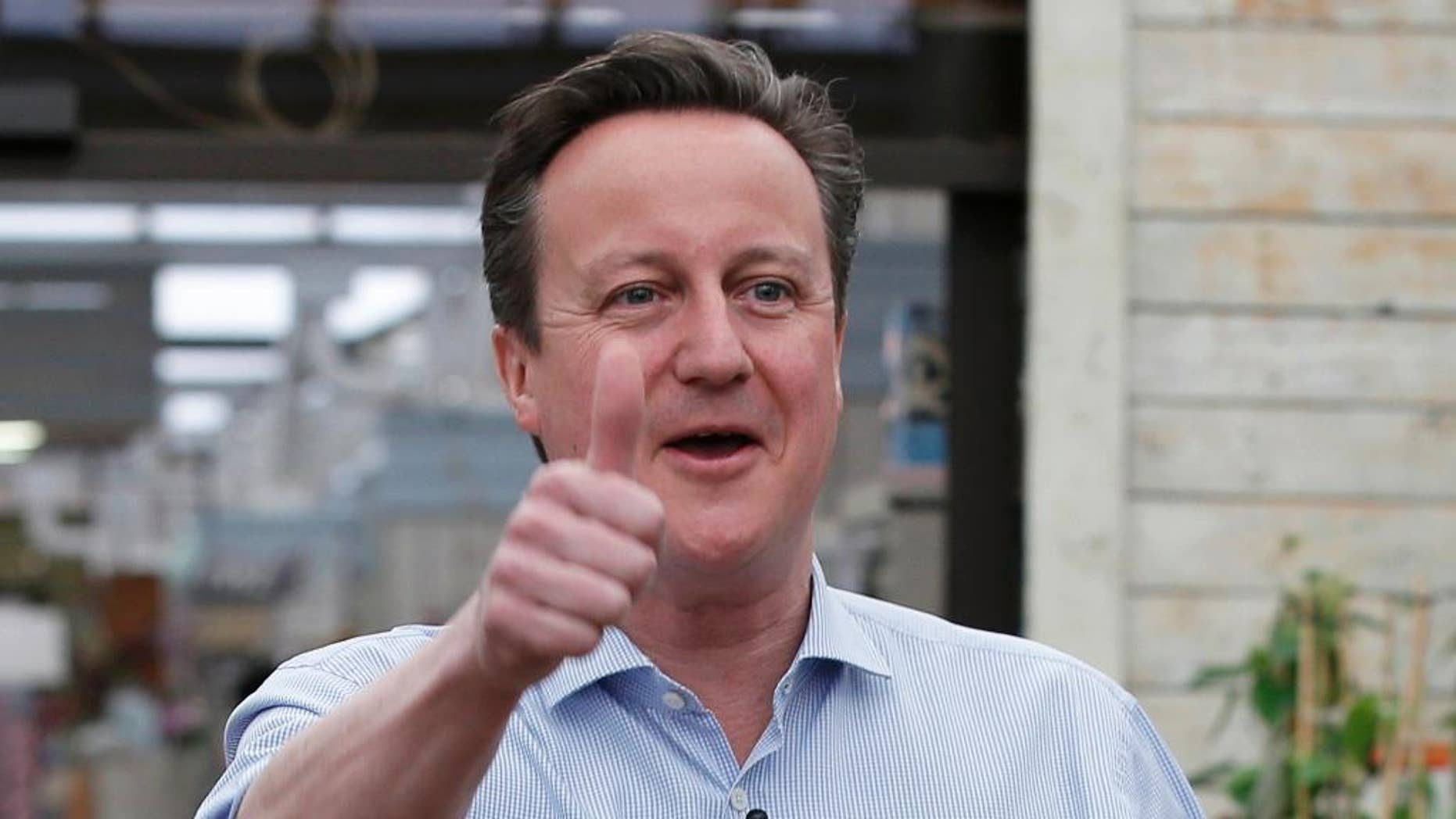 Britain's Prime Minister and Conservative Party leader David Camer  gestures to supporters  in Twickenham, London, Tuesday May 5, 2015. Britain will go to the polls in a national election on May 7. (AP Photo/Peter Nicholls, Pool)