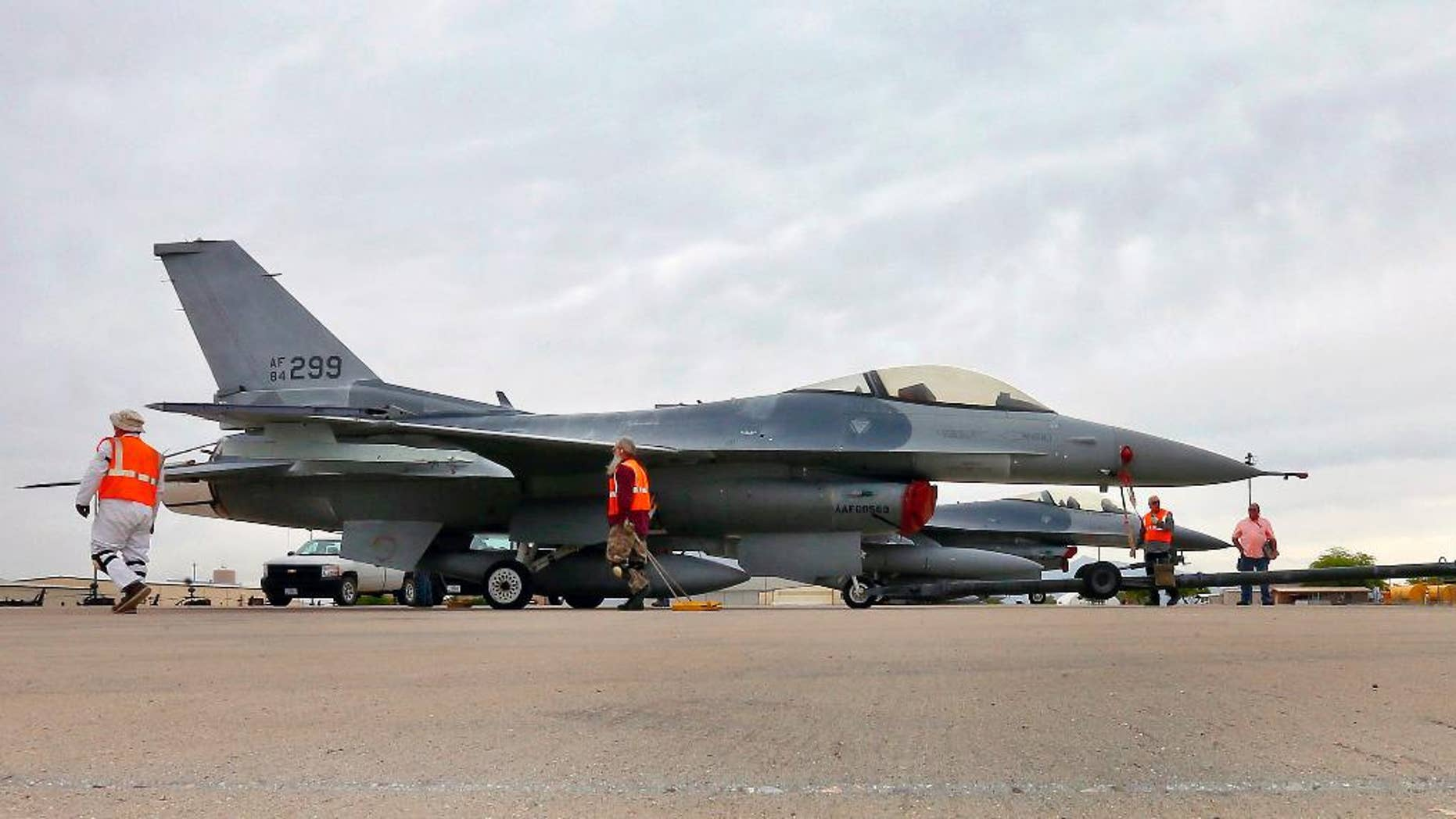 FILE - In this May 15, 2015, file photo, a boneyard crew tows an F-16 Fighting Falcon aircraft prior to the preservation process after its arrival at the 309th Aerospace Maintenance and Regeneration Group at Davis-Monthan Air Force Base in Tucson, Ariz. Military officials confirm a single F-16 Fighting Falcon aircraft crashed Wednesday night, June 24, 2015, about 5 miles east of Douglas Municipal Airport. The pilot with the 162nd Wing Arizona Air National Guard was the only person on board during the night training mission, according to an Arizona Air National Guard statement.  The pilot's identity and condition is unknown at this time.  (AP Photo/Matt York, File)