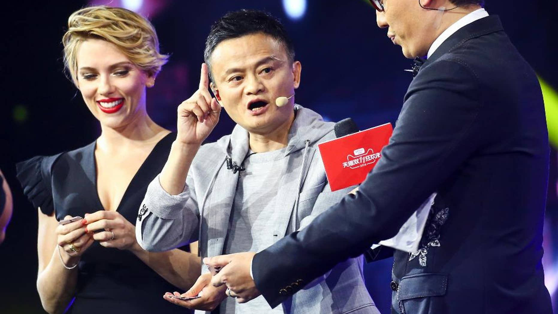 In this Thursday, Nov. 10, 2016 photo, Hollywood actress Scarlett Johansson, left, and Alibaba Group Chairman Jack Ma, center, attend an evening gala on the eve of the Singles Day online shopping festival in Shenzhen in southern China's Guangdong province.