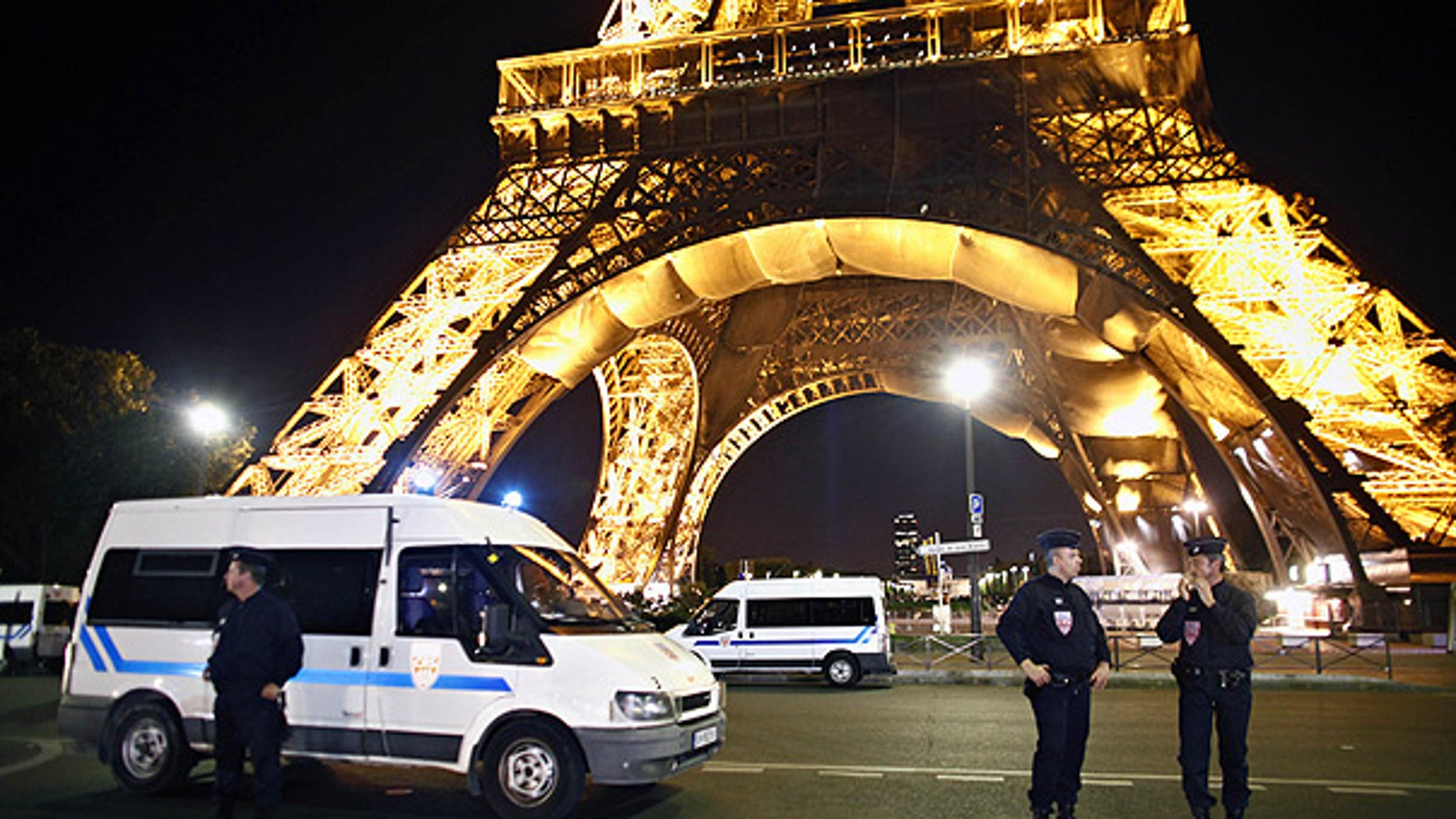 Police officers stand in front of the Eiffel Tower, in Paris, after an anonymous caller phoned in a bomb threat.