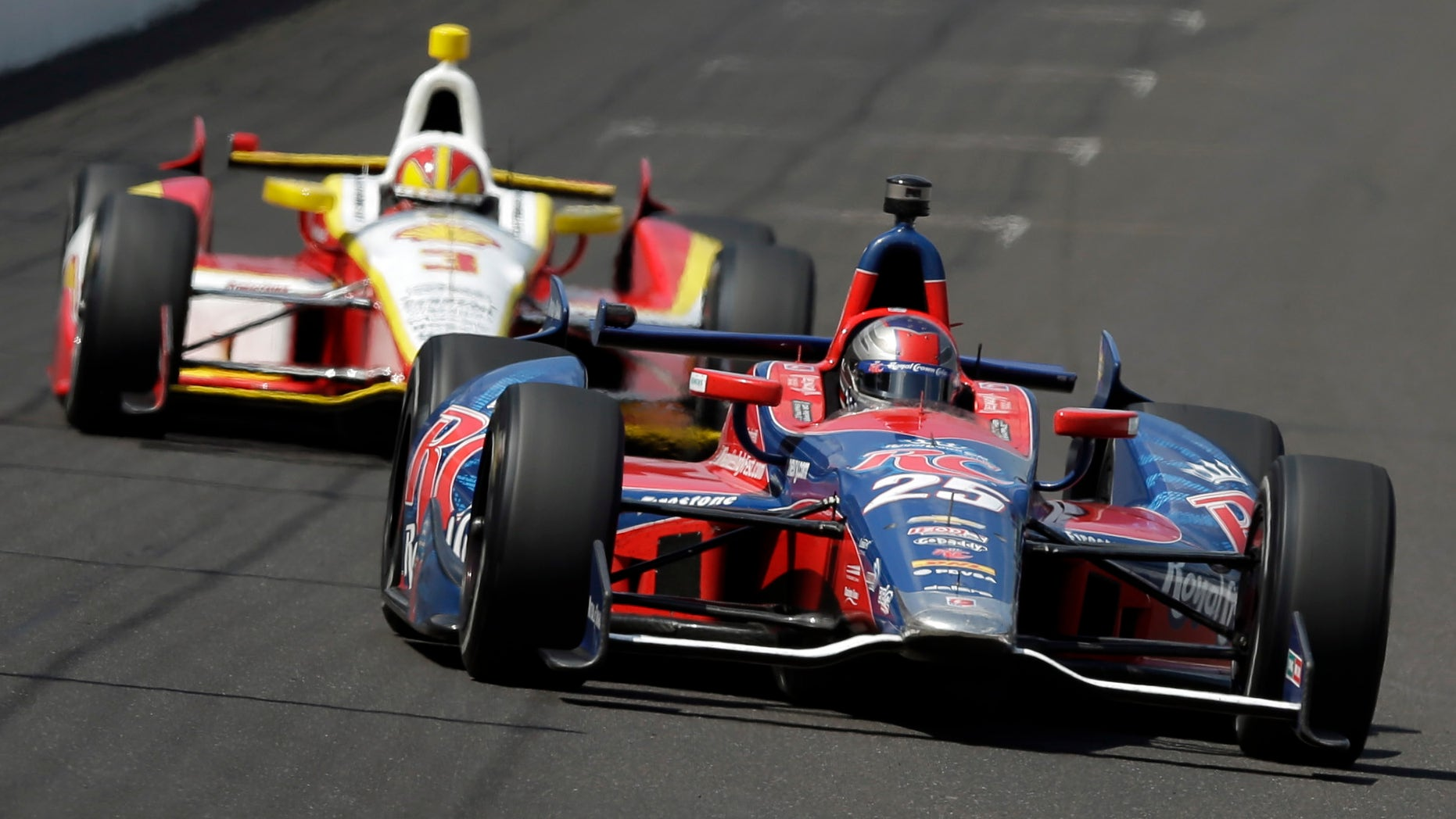 In this May 19, 2013 photo, Marco Andretti, leads Helio Castroneves, of Brazil, into the first turn on the second day of qualifications for the Indianapolis 500 auto race at the Indianapolis Motor Speedway in Indianapolis. Graham Rahal and Andretti have all the ingredients the IndyCar Series has been craving. They have famous family names, have reached Victory Lane and seem to enjoy playing up their growing rivalry.  (AP Photo/Darron Cummings)