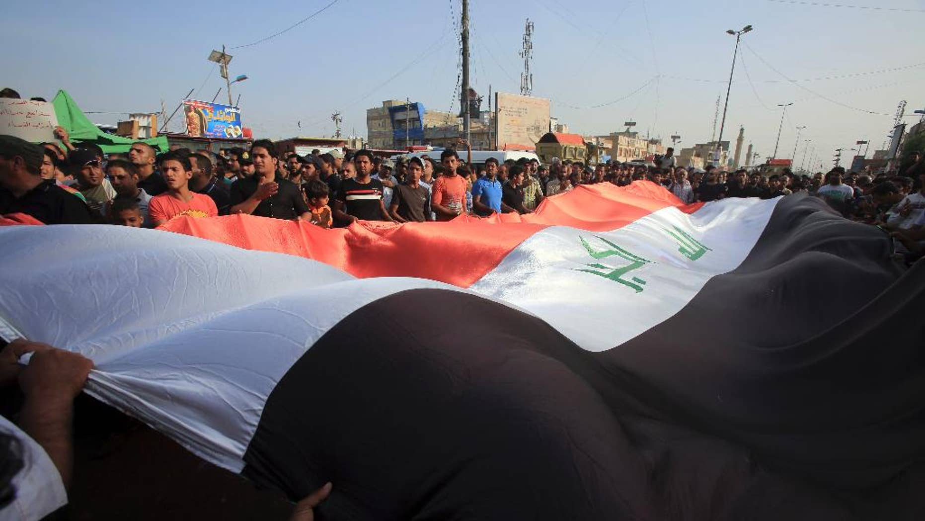 Protesters wave a giant Iraq flag as they chant anti-government slogans during a demonstration against the security forces' failure to protect them from car bombs Thursday.