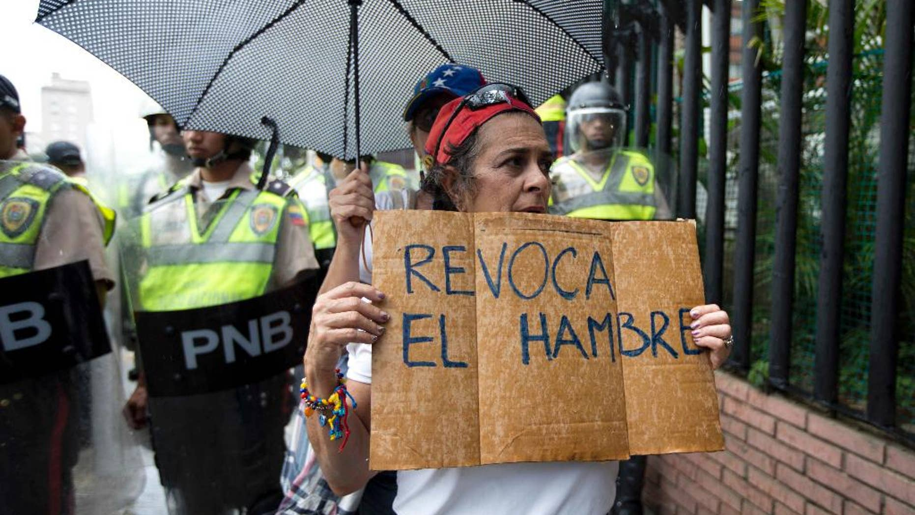 "FILE - In this July 27, 2016, file photo, a woman holds a sign with a message that in reads in Spanish ""Revoke hunger"" during a protest march in Caracas, Venezuela. Venezuela's electoral authorites, on Monday,Aug. 1, have validated the signatures for a recall referendum process against President Nicolas Maduro. (AP Photo/Ariana Cubillos, File)"